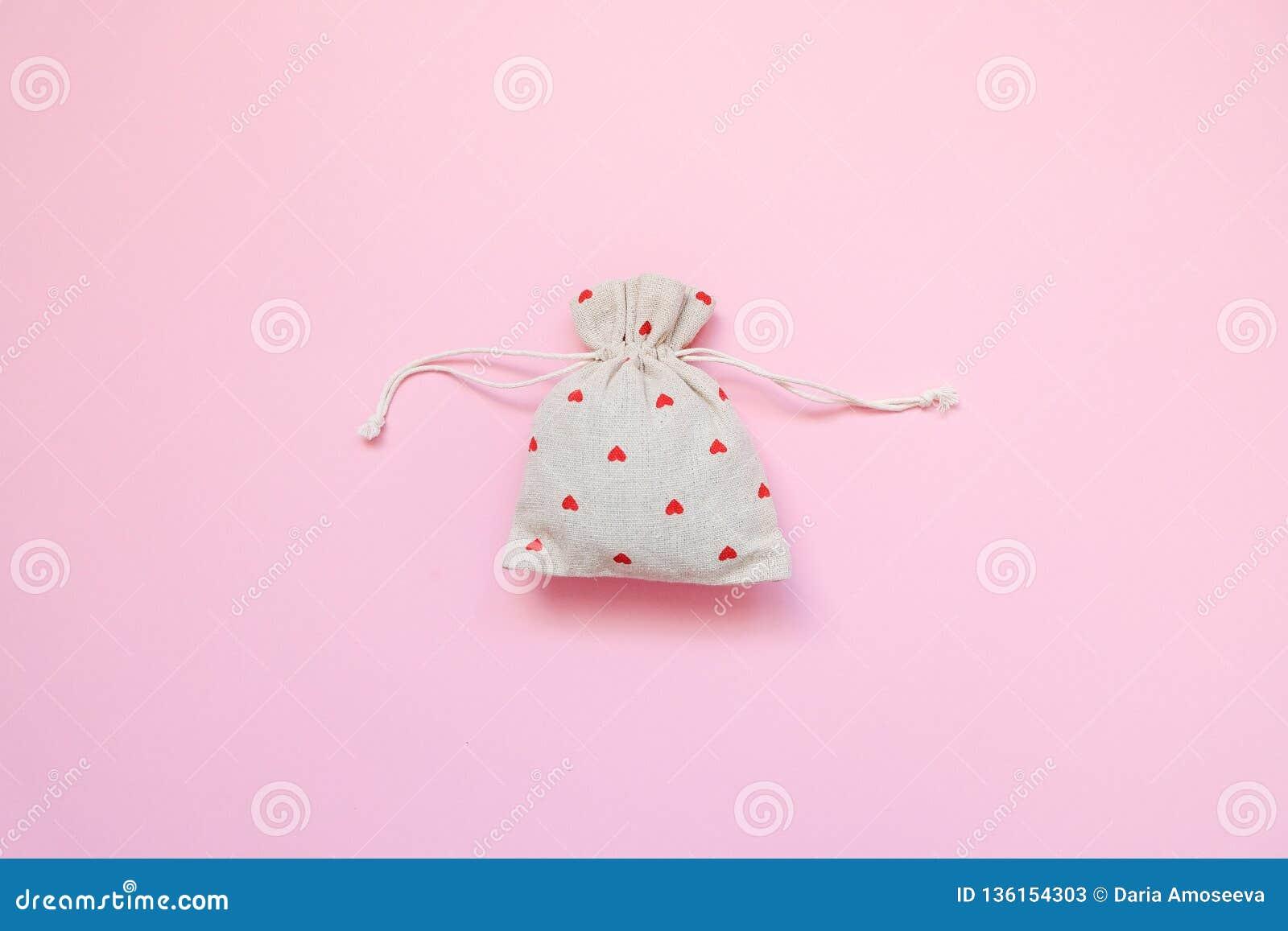Linnenzak met rode harten op roze achtergrond De dag van de valentijnskaart `s r Vlak leg, hoogste mening