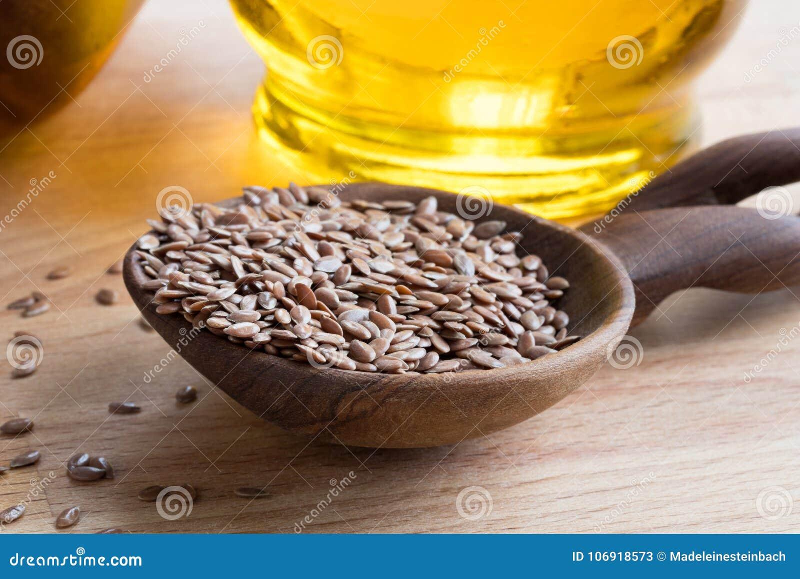Linseed na drewnianej łyżce z flaxseed olejem w tle,