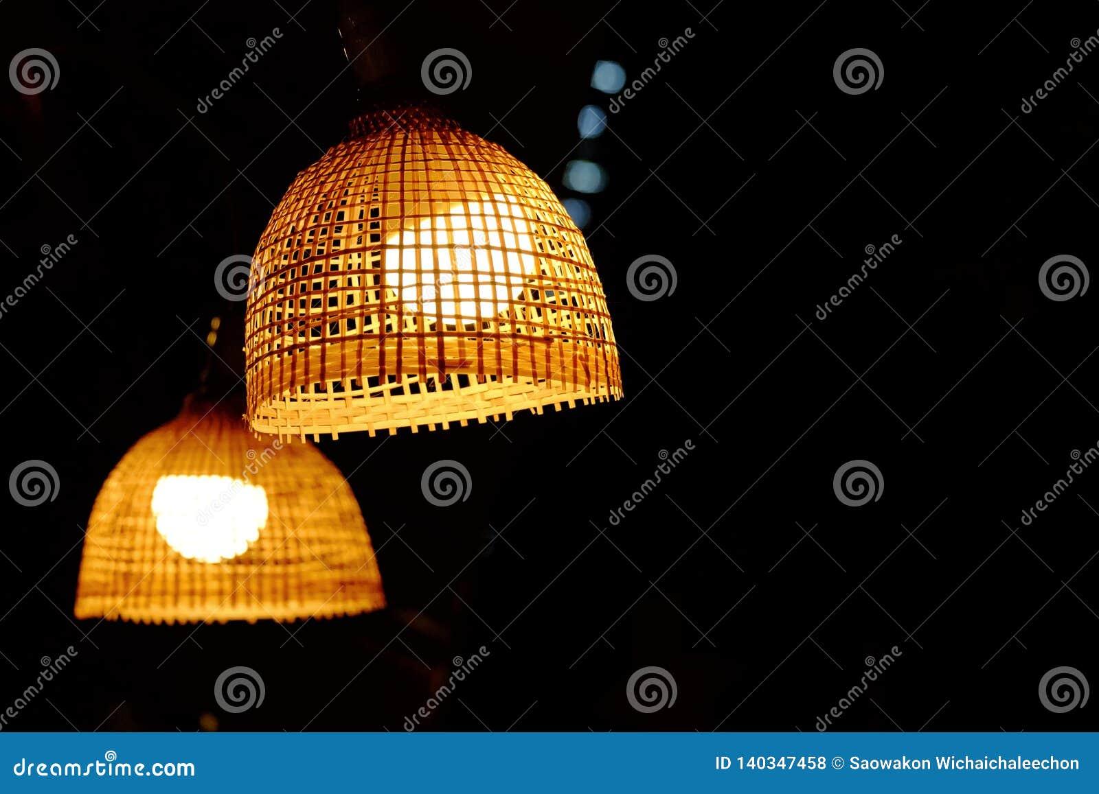 Linterna de bambú con un bulbo que cuelga de un techo del sitio con el fondo oscuro