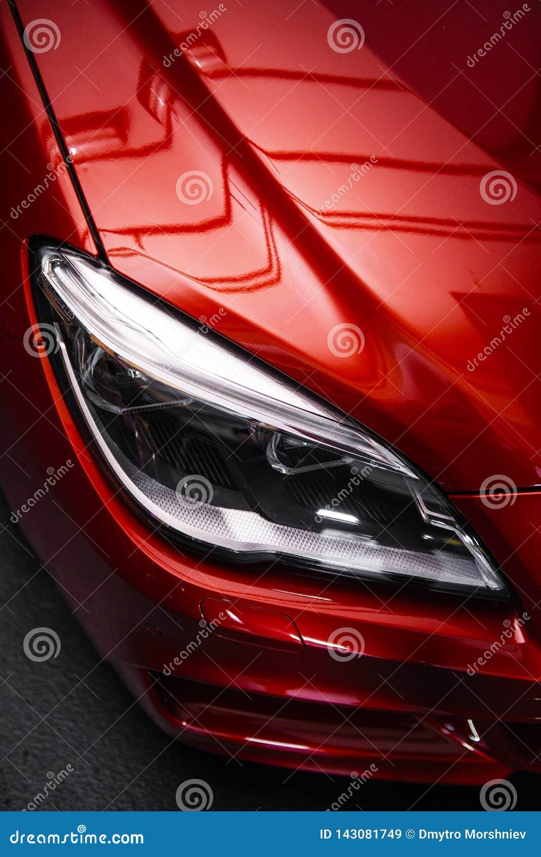 Linterna trasera de un coche rojo de lujo moderno, detalle auto, concepto del mantenimiento del coche en el garaje
