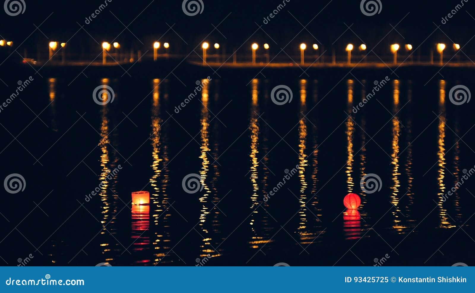 Linternas de la agua ligera en el río en la noche