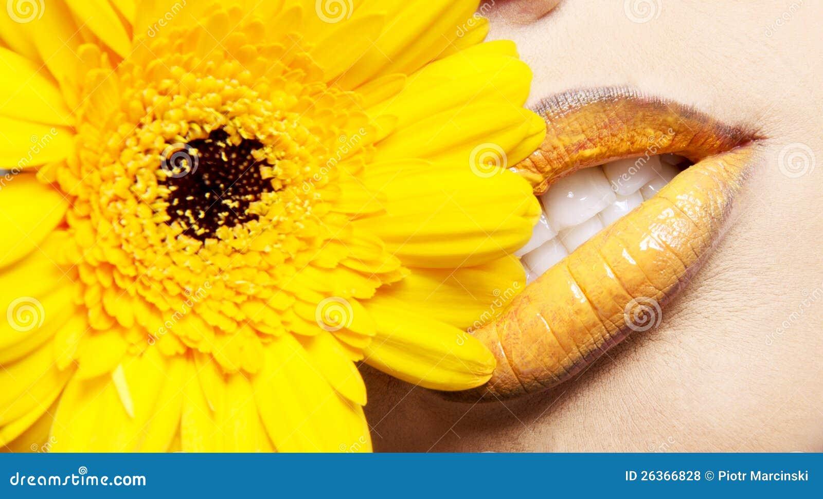 Lippen der Frau mit gelber Blume
