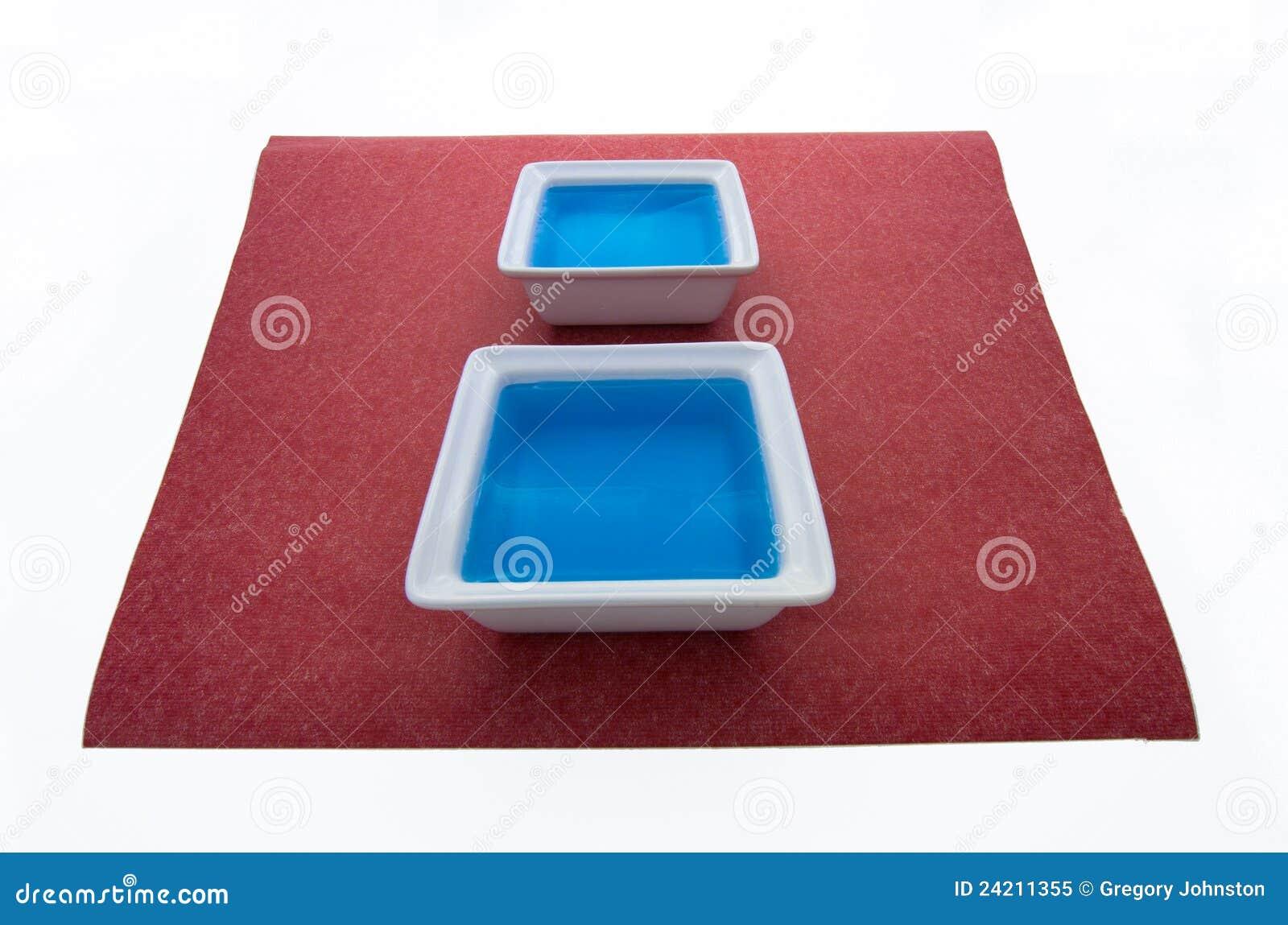 Liquide bleu sur le papier rouge.