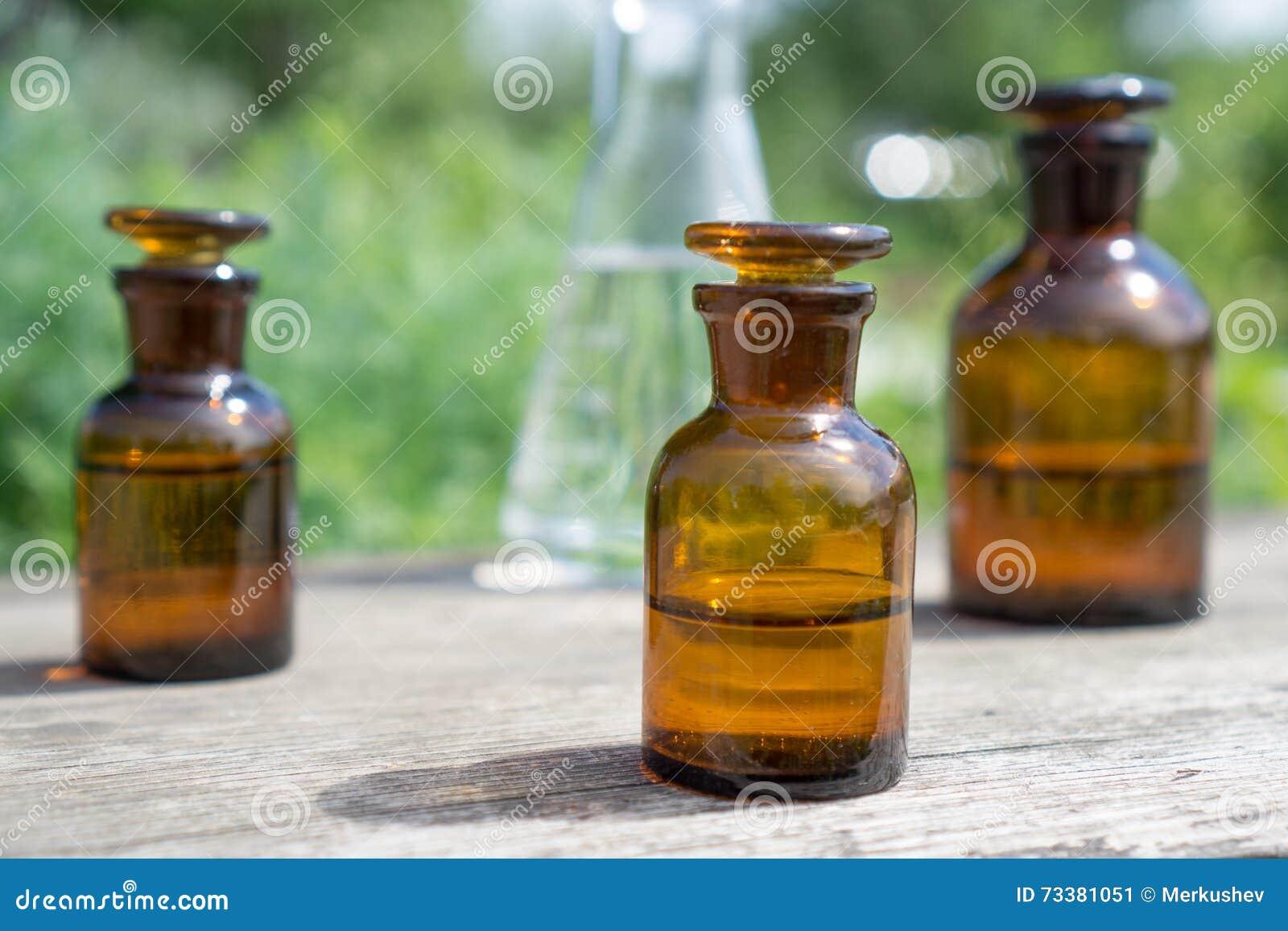 Liquide en articles chimiques sur un fond des usines, des engrais ou des pesticides dans le jardin