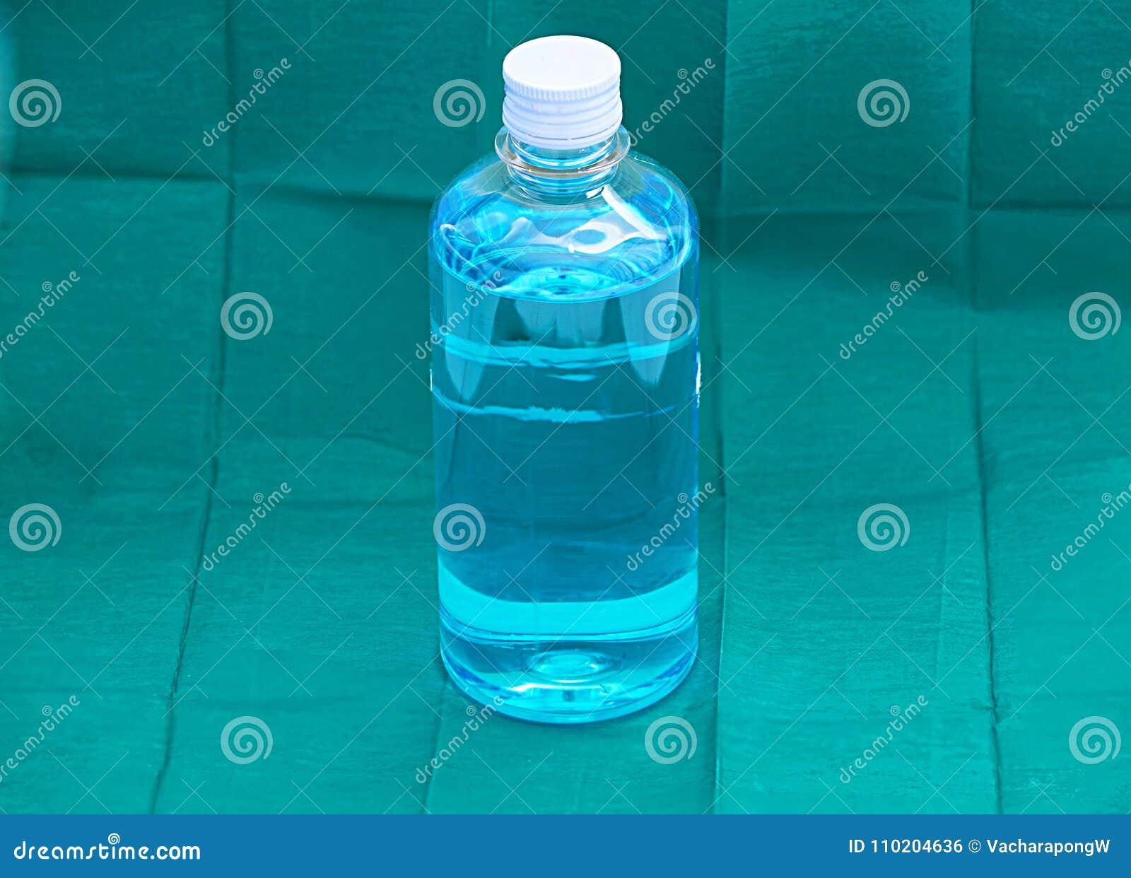 Liquido blu dell alcol etilico in bottiglia trasparente di plastica su verde