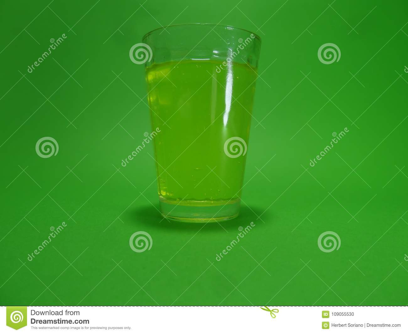 Absinthein a transparent glass on a green background
