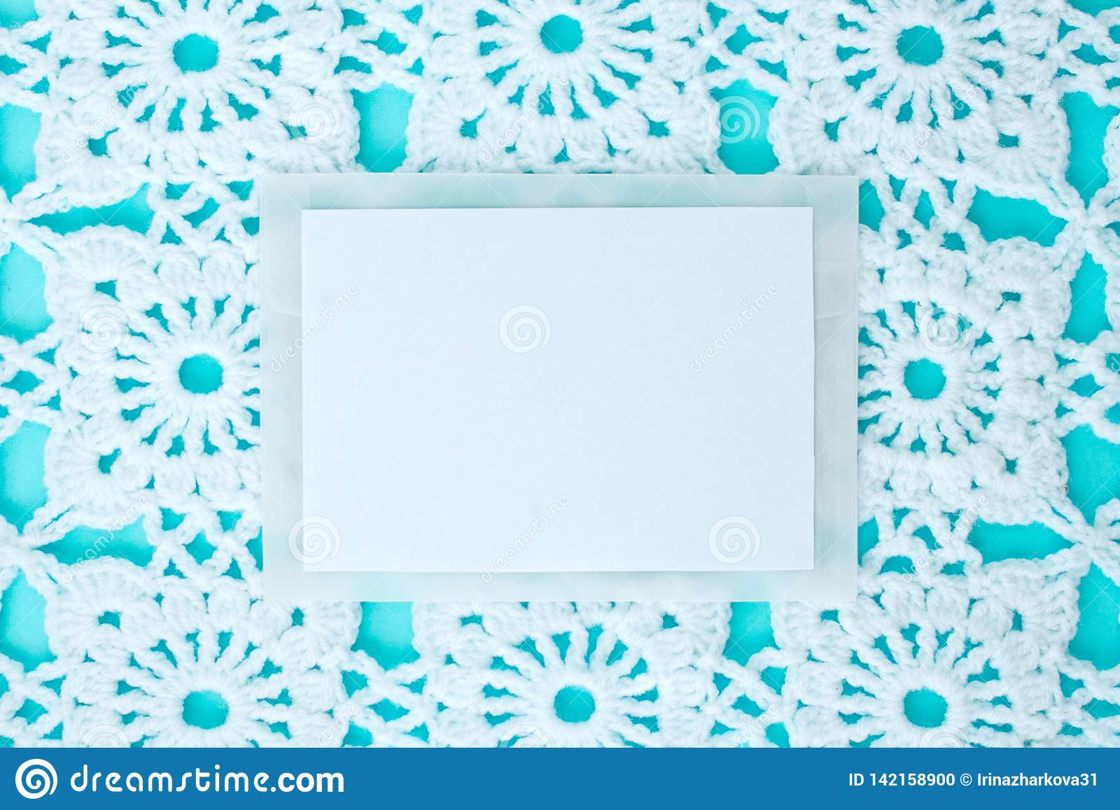 Liso, colocado, uma folha de papel para o texto em um fundo azul com laço branco feito crochê do vintage, tema do inverno, orname