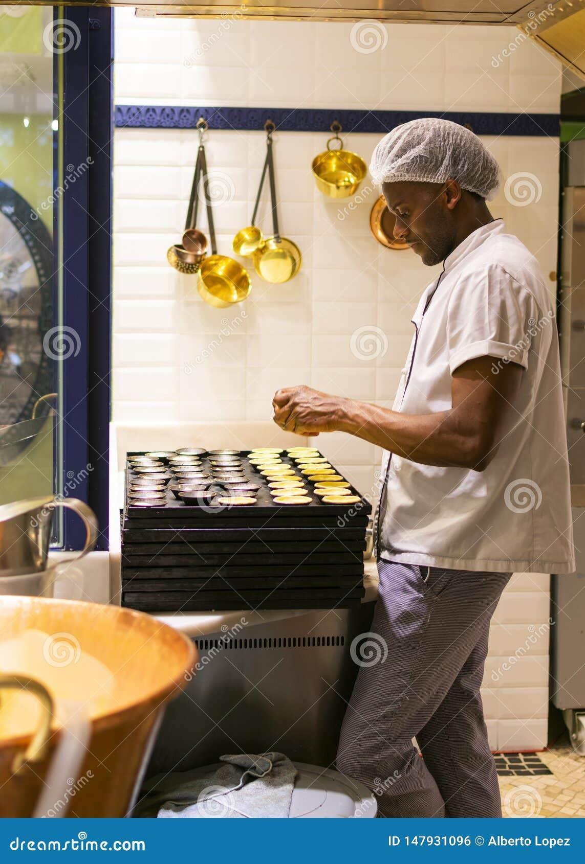 LISSABON, PORTUGAL - APRIL 17, 2019: De chef-kok bereidt traditionele Portugese gebakjes Pastel DE Nata in Lissabon voor