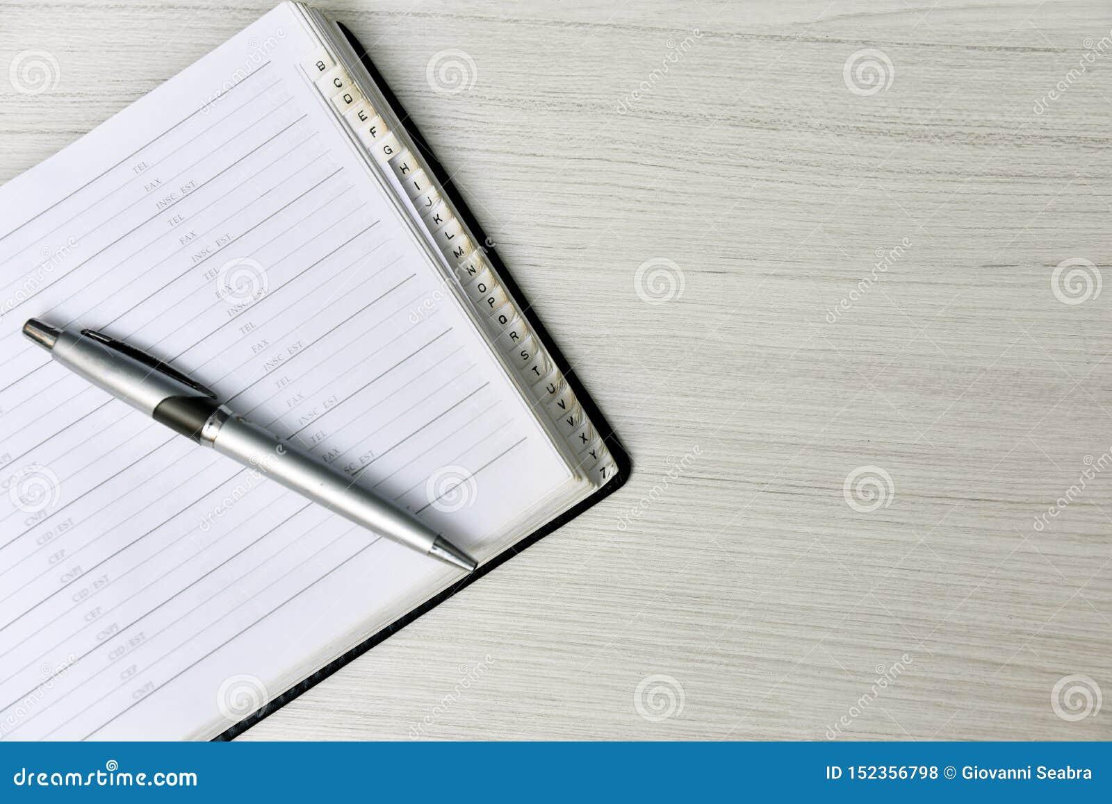 Lista telefônica com a pena na tabela branca