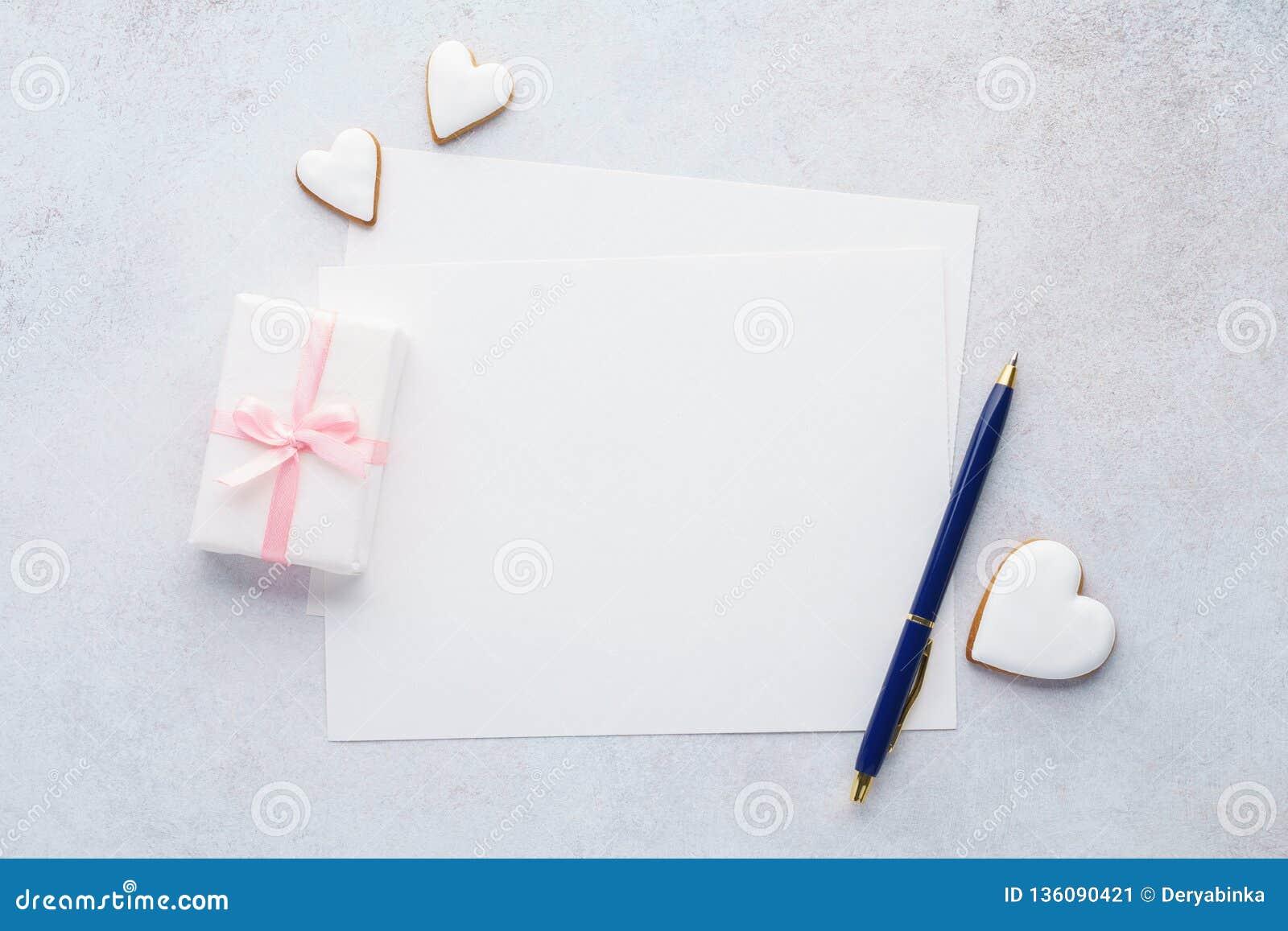 Listan av papper, gåvaasken, hjärta formade kakor och en penna
