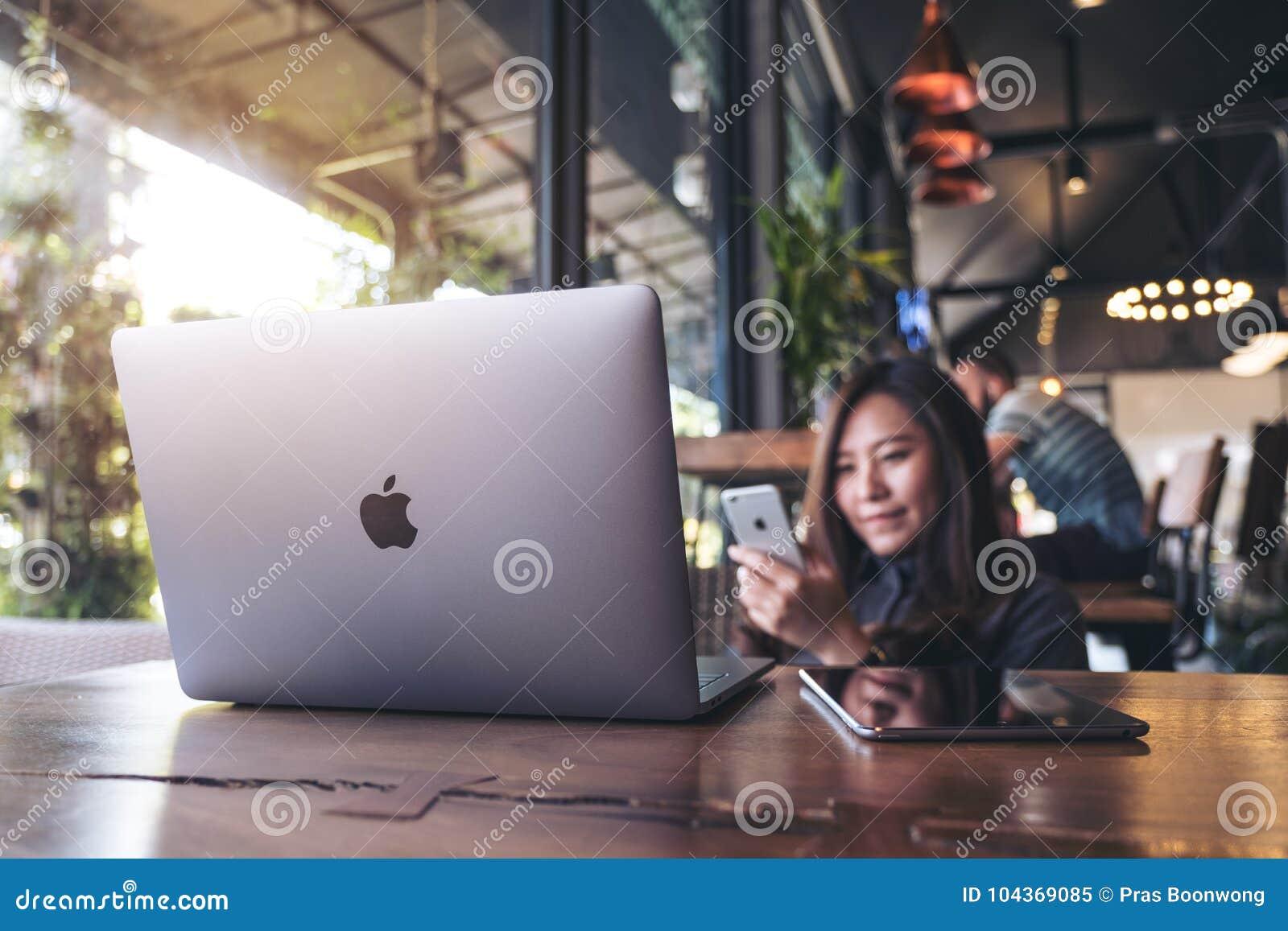 Listopad 17th 2017: Azjatycka biznesowa kobieta trzyma mądrze telefon z laptopem na drewnianym stole w nowożytnej kawiarni, Chian
