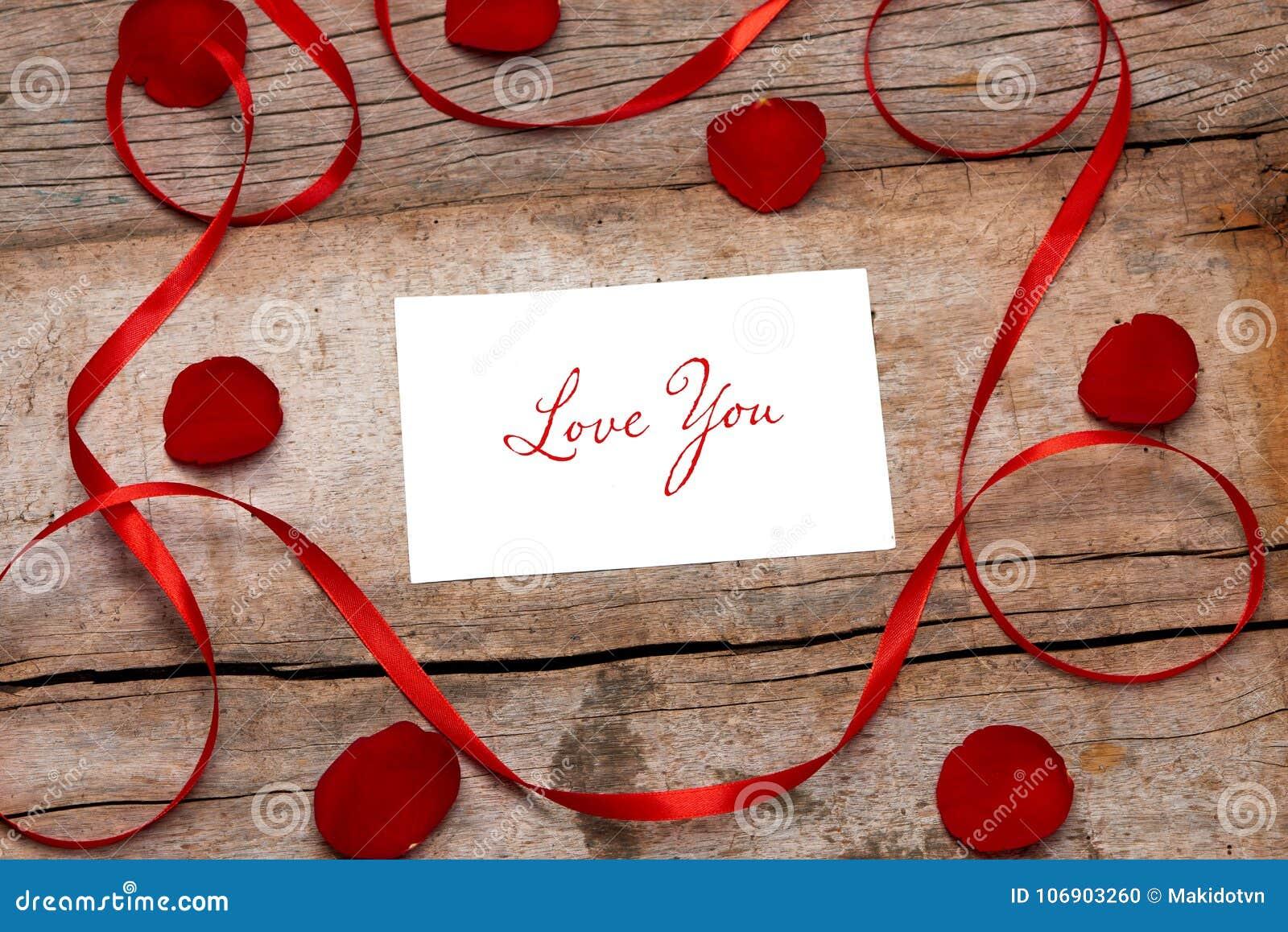 Listu miłosnego valentine wzrastał w kopercie na drewnianym tle i