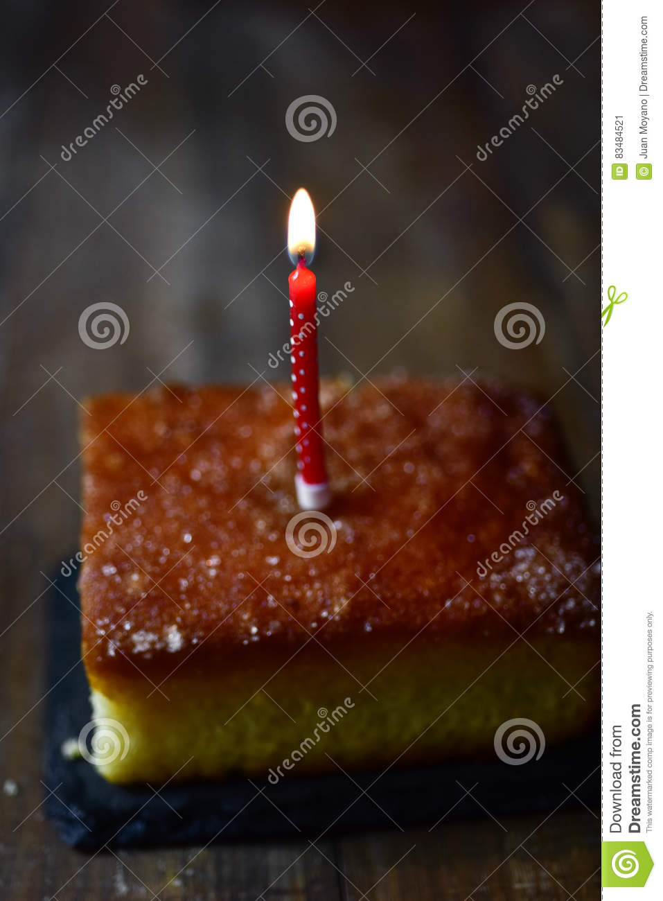 Lit birthday candle on a cake