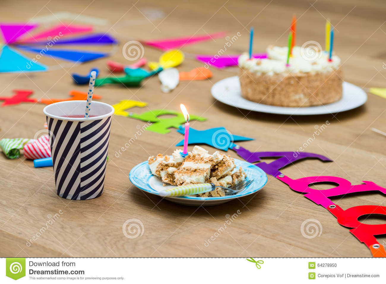 Closeup Of Lit Candles On Birthday Cake At Decorated Wooden Table
