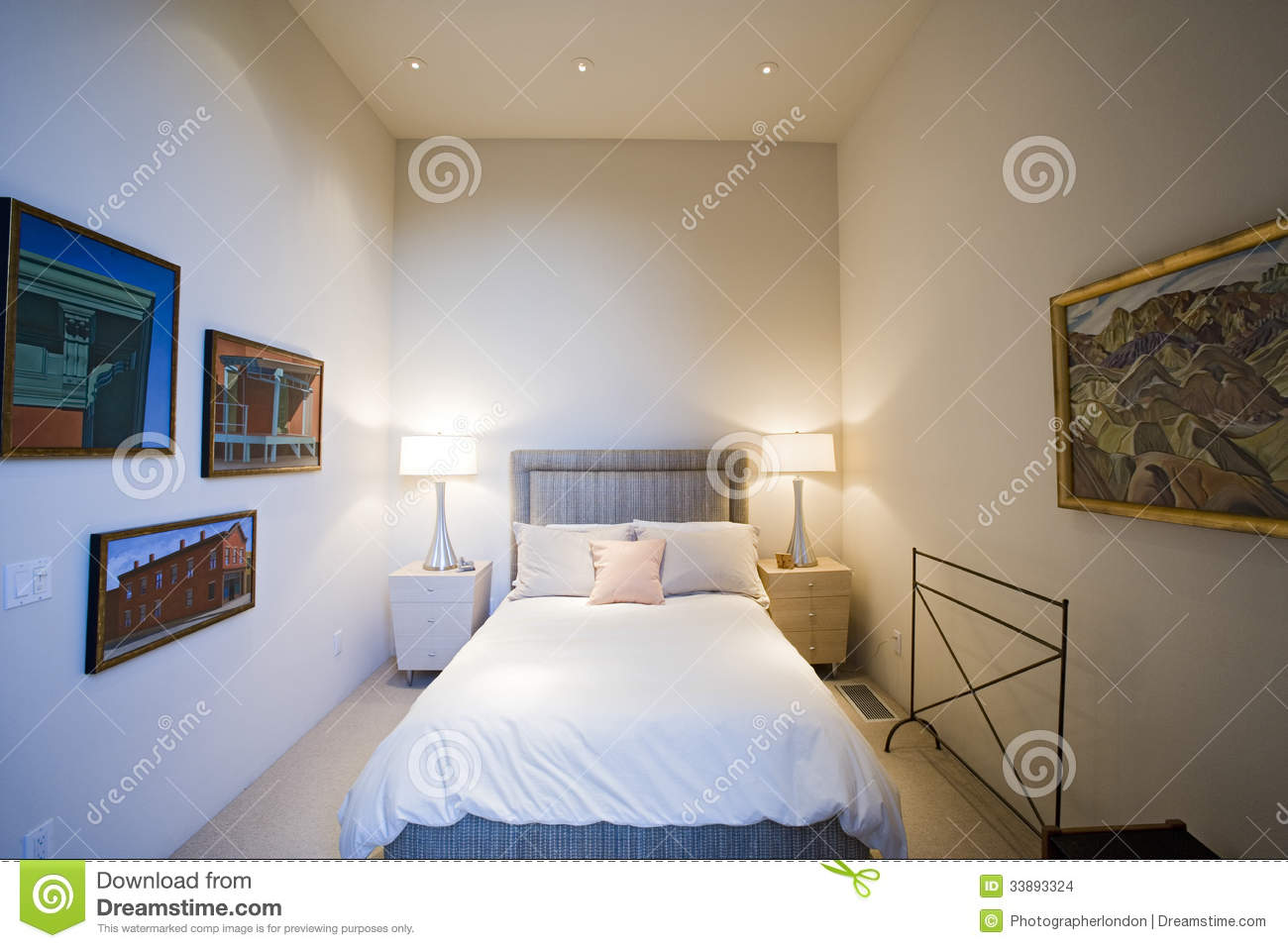 Lit Lamps By Bed With Frames On Wall In Bedroom Stock
