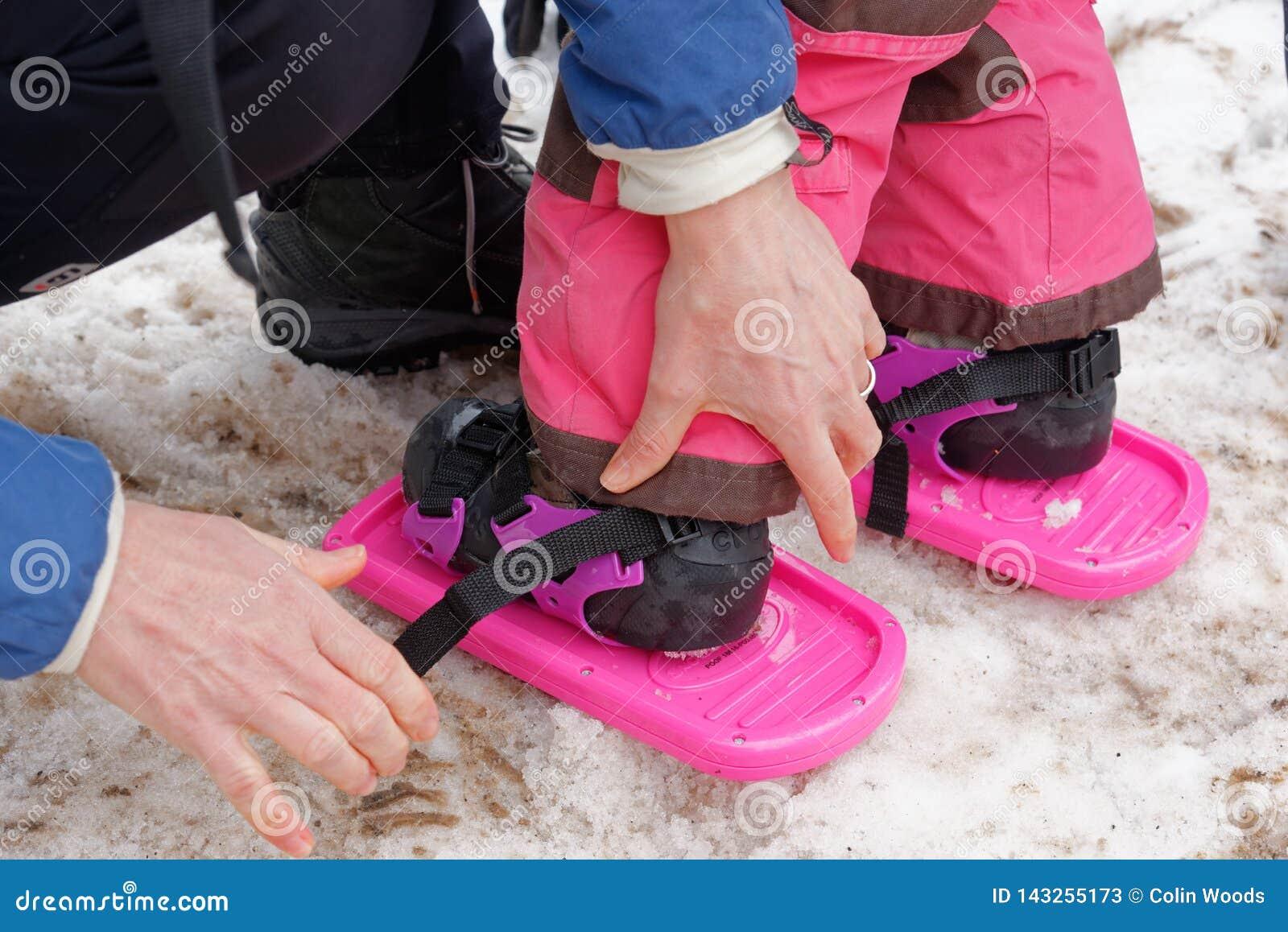 Lite årig flicka 3 ha honom fäste snöskor