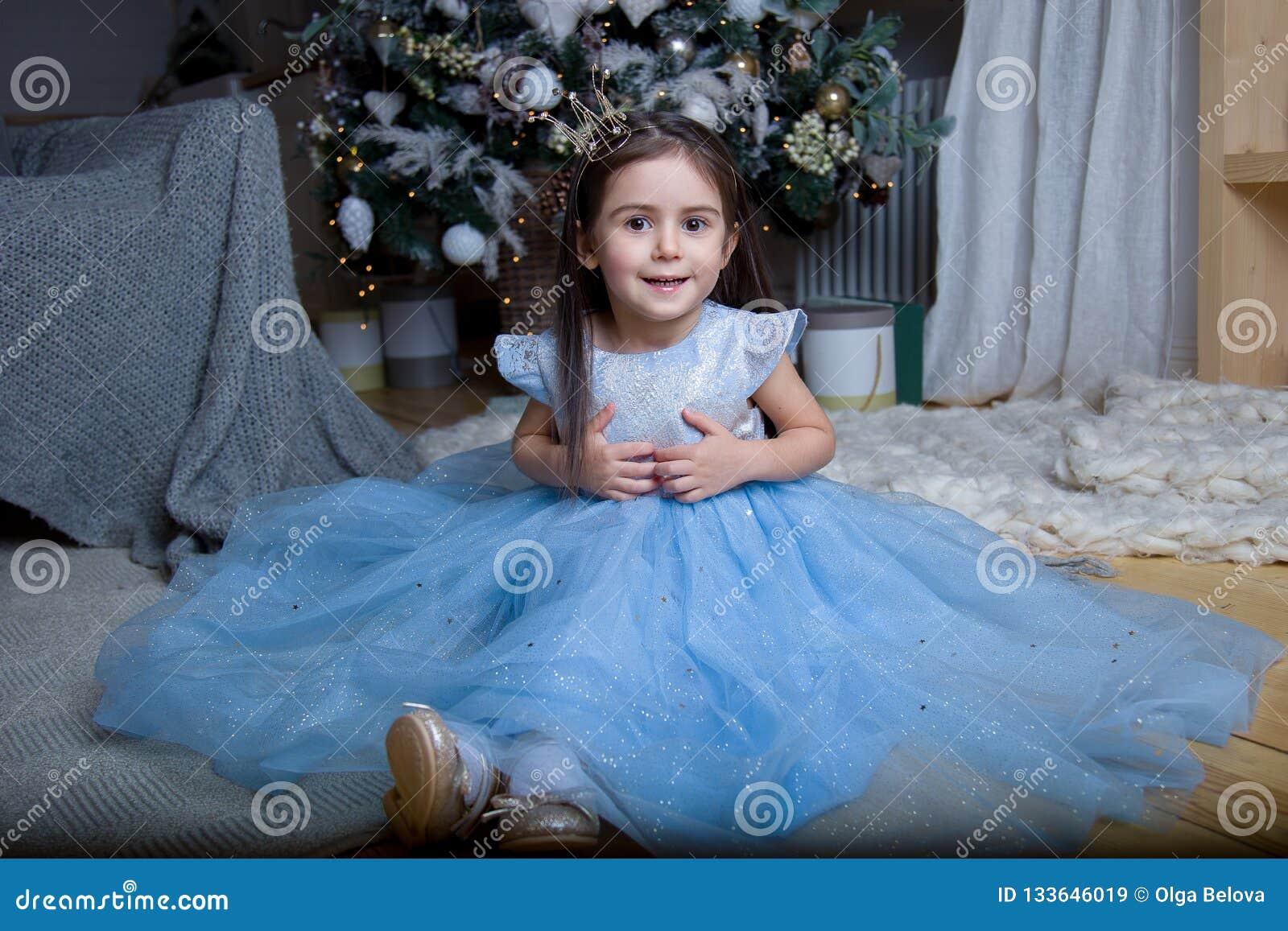 Lite flicka i en härlig blå klänning på julgranen