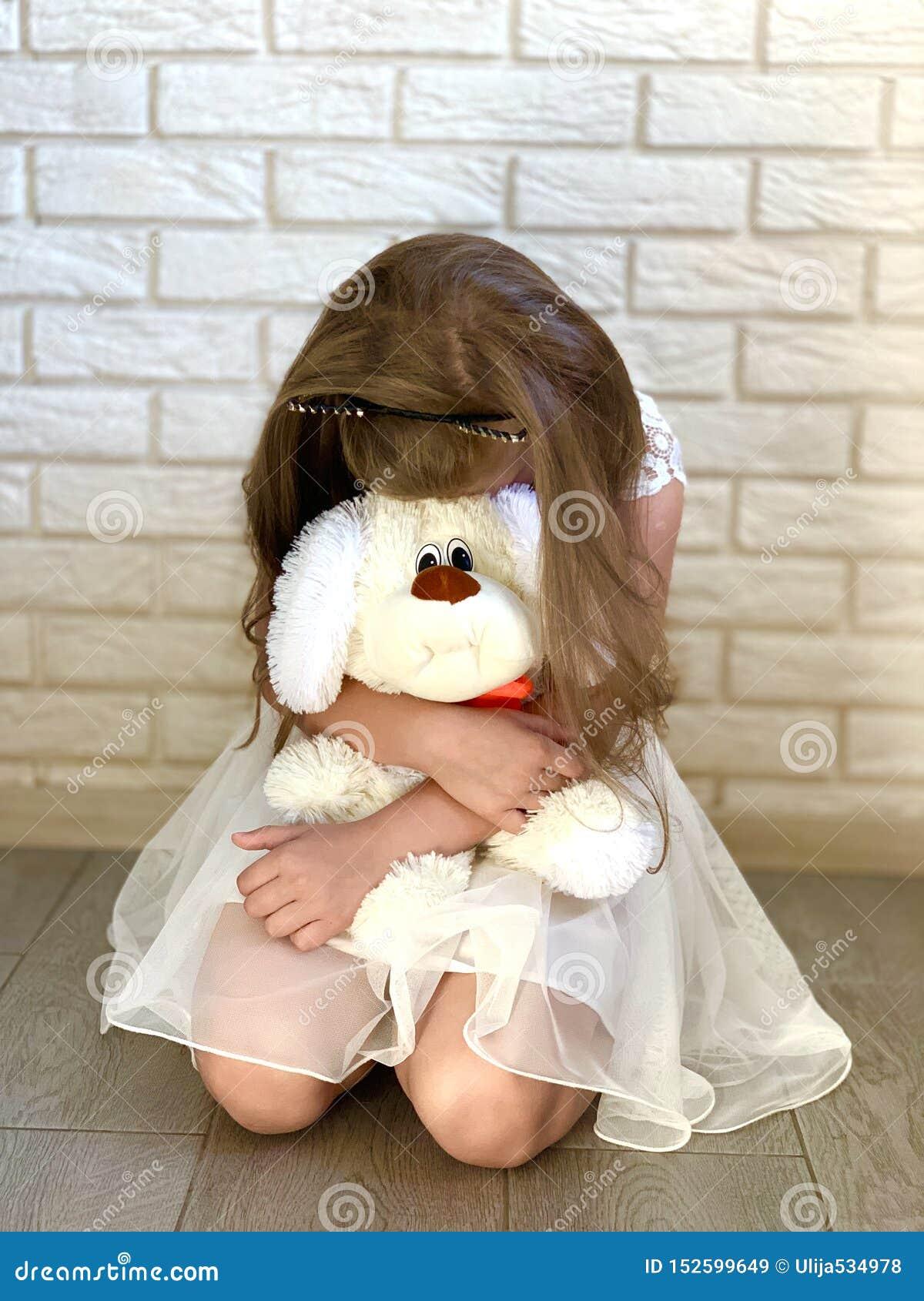 Lite flicka i en vit kl?nning En flicka med en toy