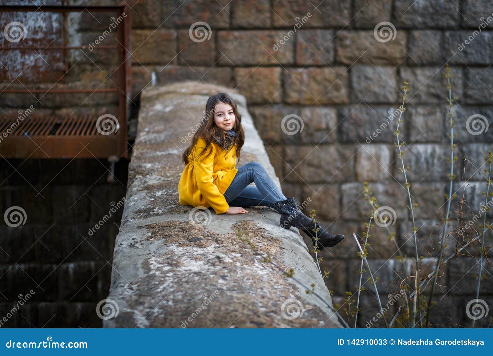Lite flicka i ett gult lag under den järnväg järnbron på solnedgången