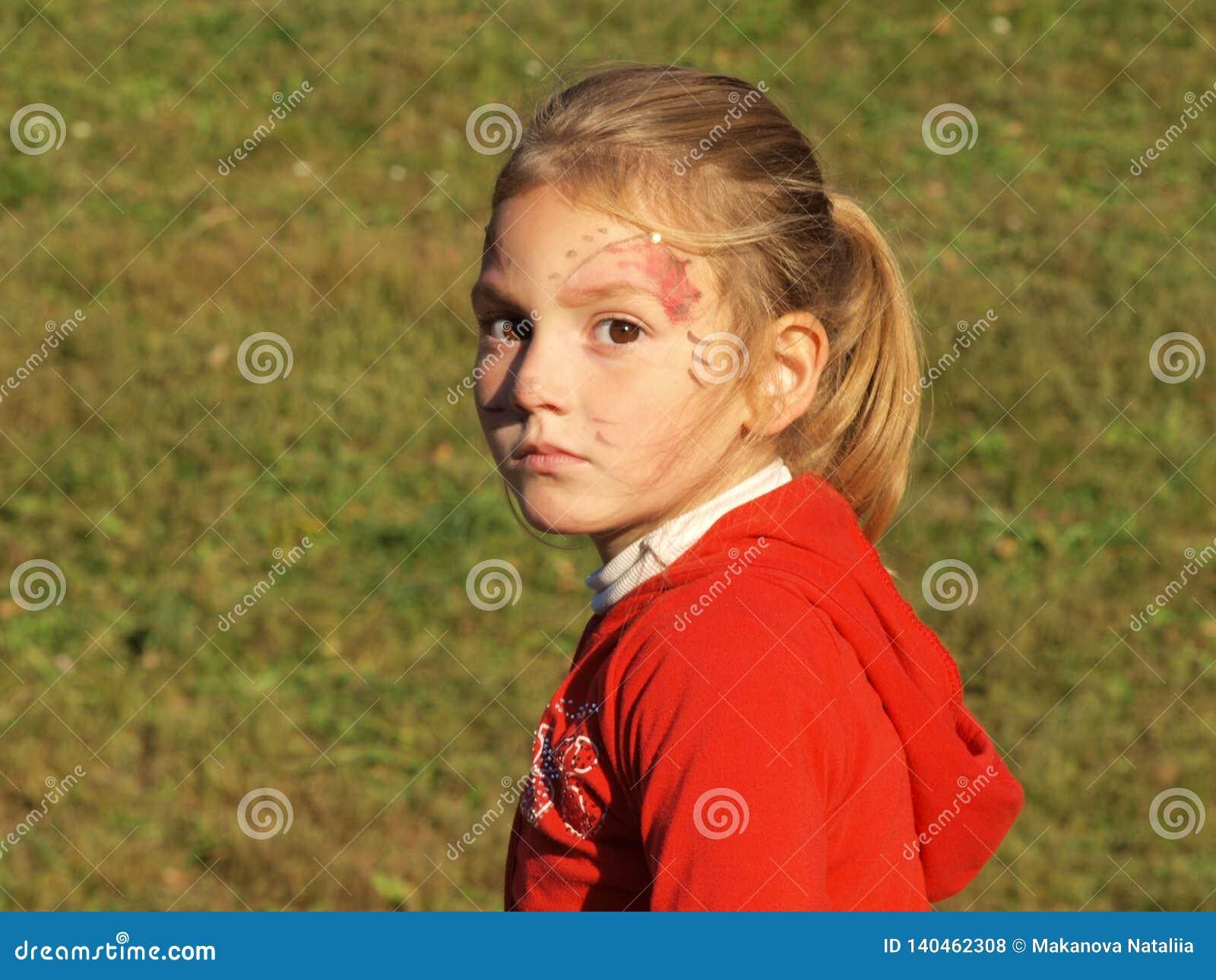 Lite flicka med en framsidamakeup och en eftertänksam blick