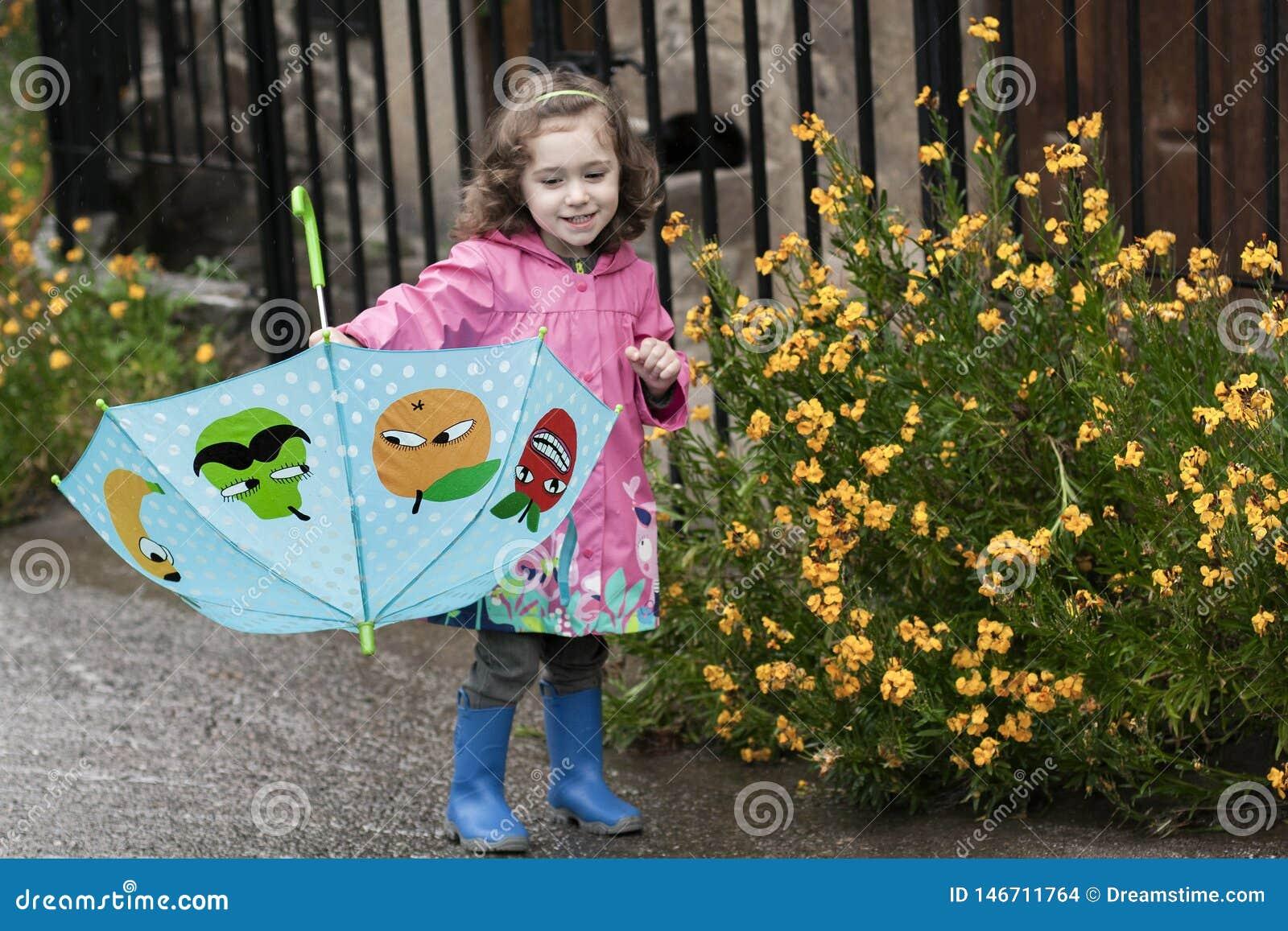 Lite flicka som spelar med ett färgrikt paraply