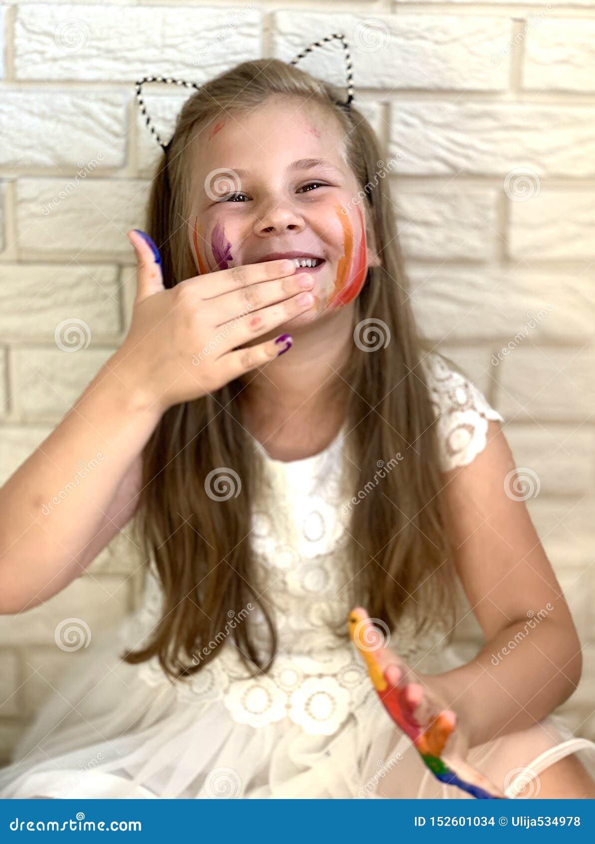Lite har flickan gyckel, kulör målarfärg på hennes händer