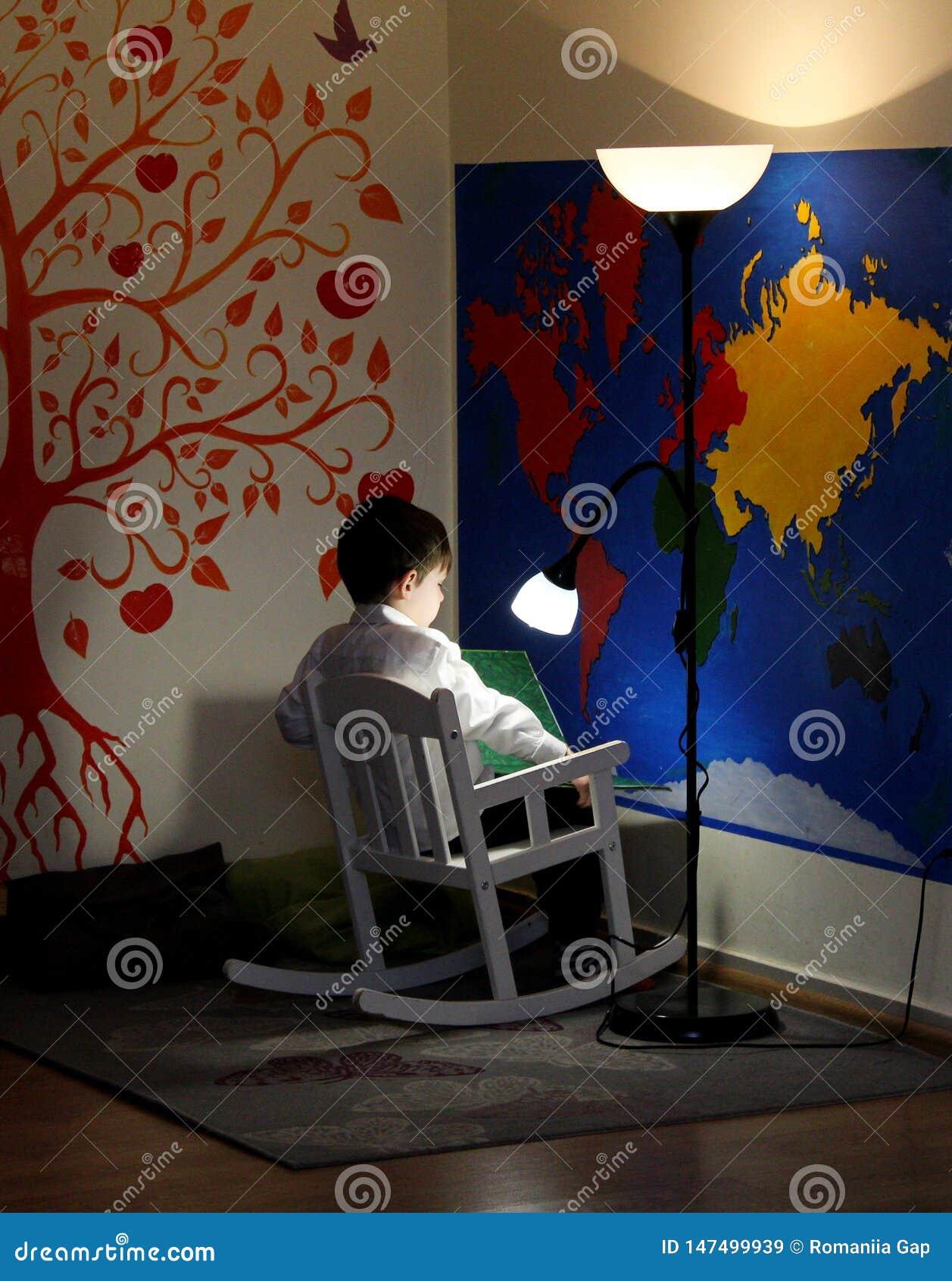 Lite läser pojken som sitter i en gungstol, och en lampa skiner ovanför honom Väggar - en översikt av världen och ett orange roli