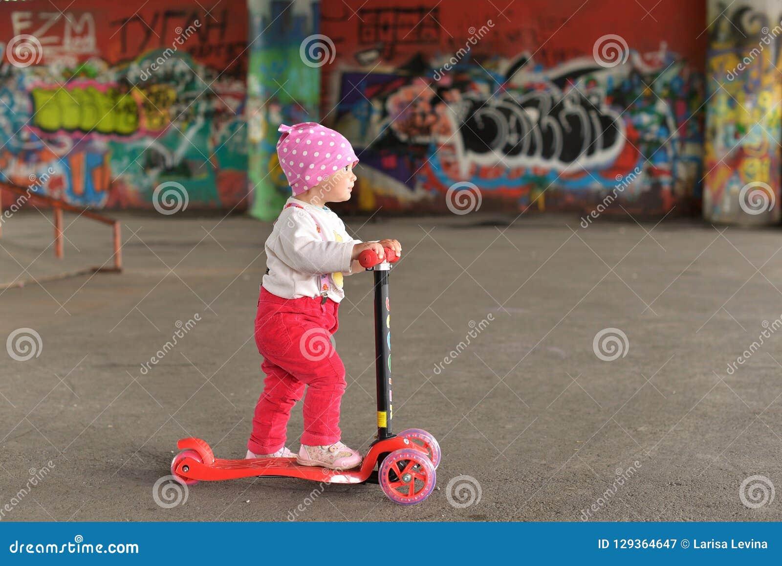 Lite parkerar flickan som rider en sparkcykel för barn` s i en skridsko