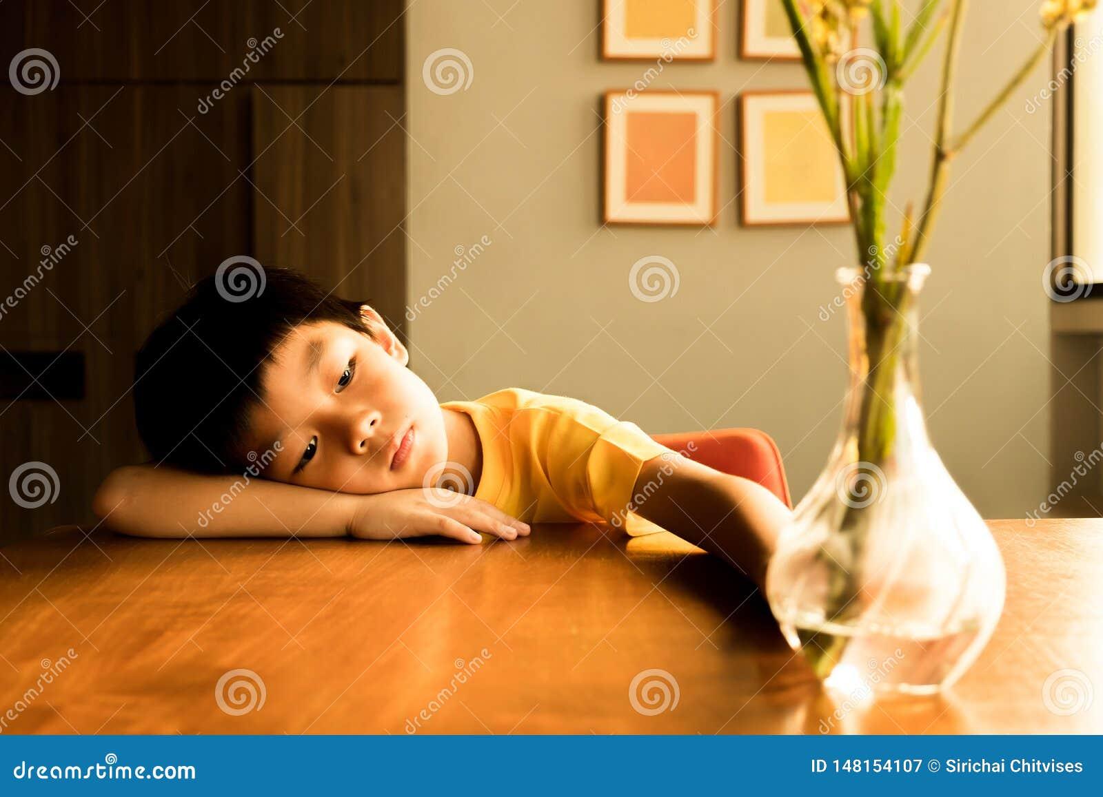 Lite pojke som hemma sitter p? tr?tabellen under solljuset i aftonen med ensam k?nsla han har inga v?nner som spelar