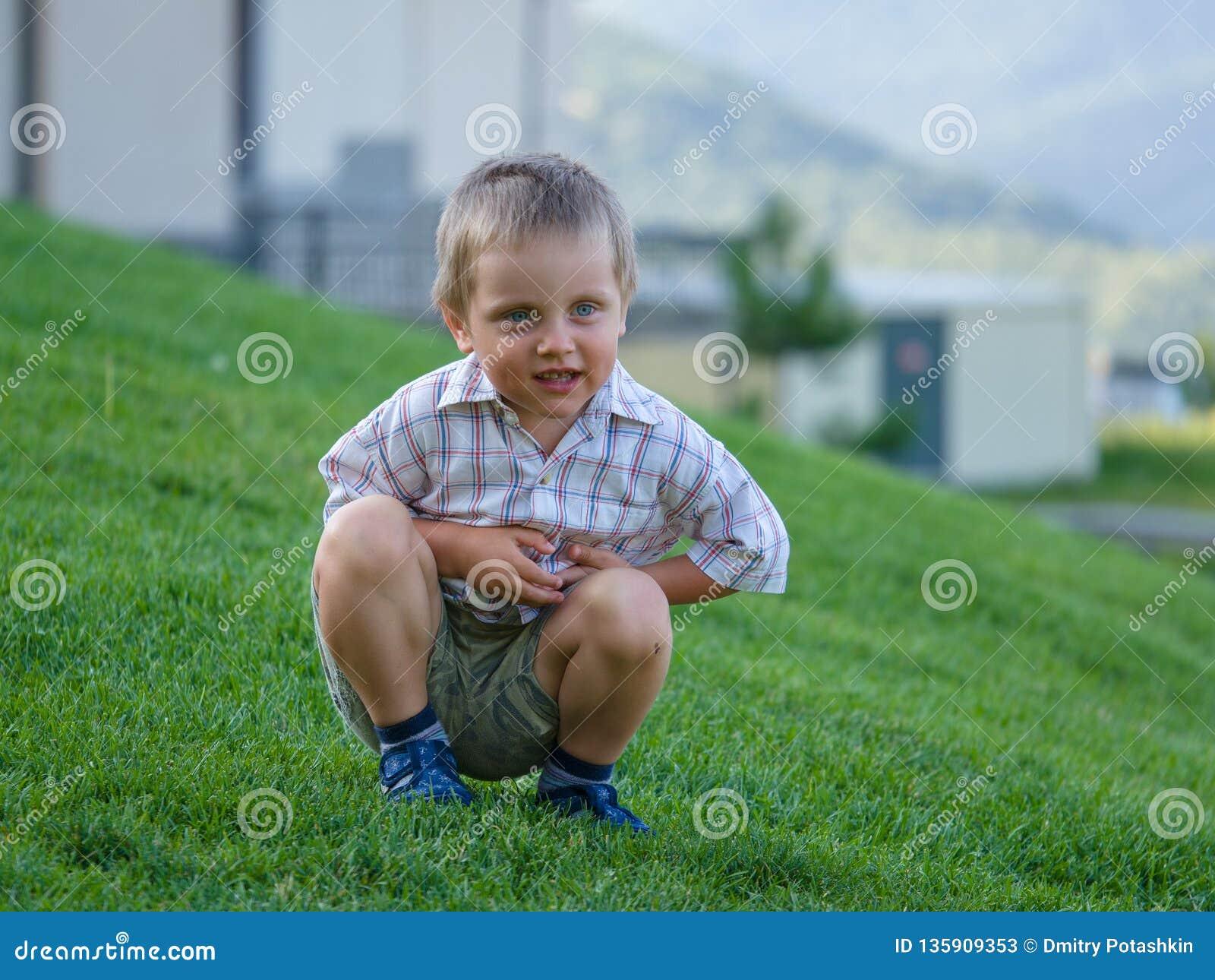 Lite pojke som sitter på en grön lutning