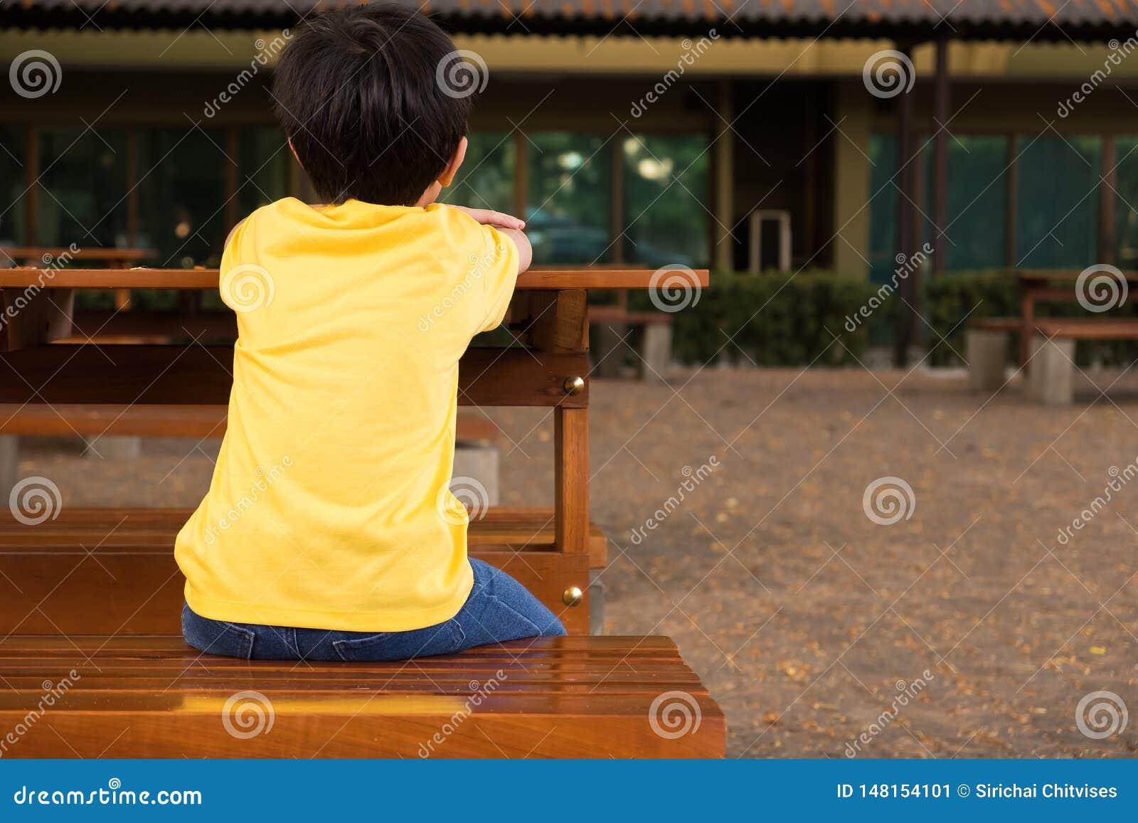 Lite pojke som sitter på trätabellen med ensam känsla på skola honom som väntar på hans föräldrar efter skola