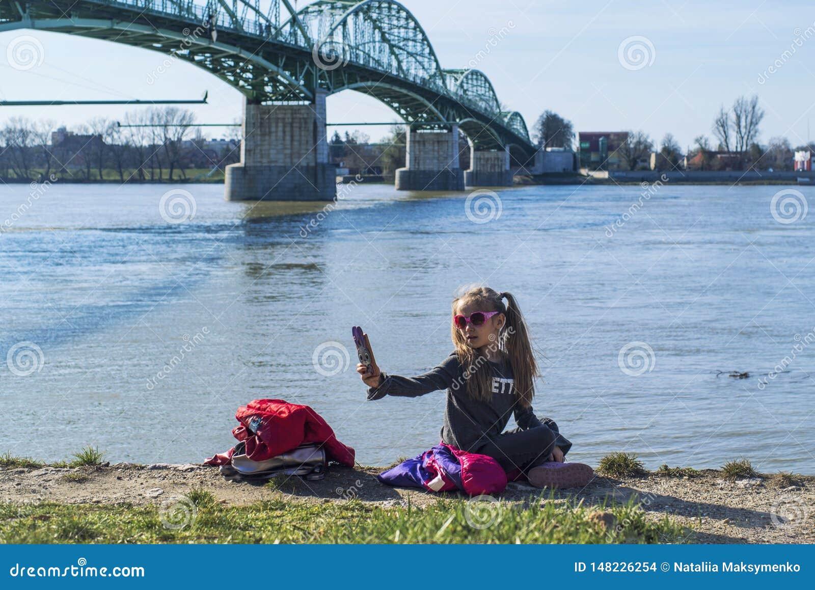 Lite sitter flickan p? banken av floden med en telefon P? en varm v?rdag En flicka g?r en selfie