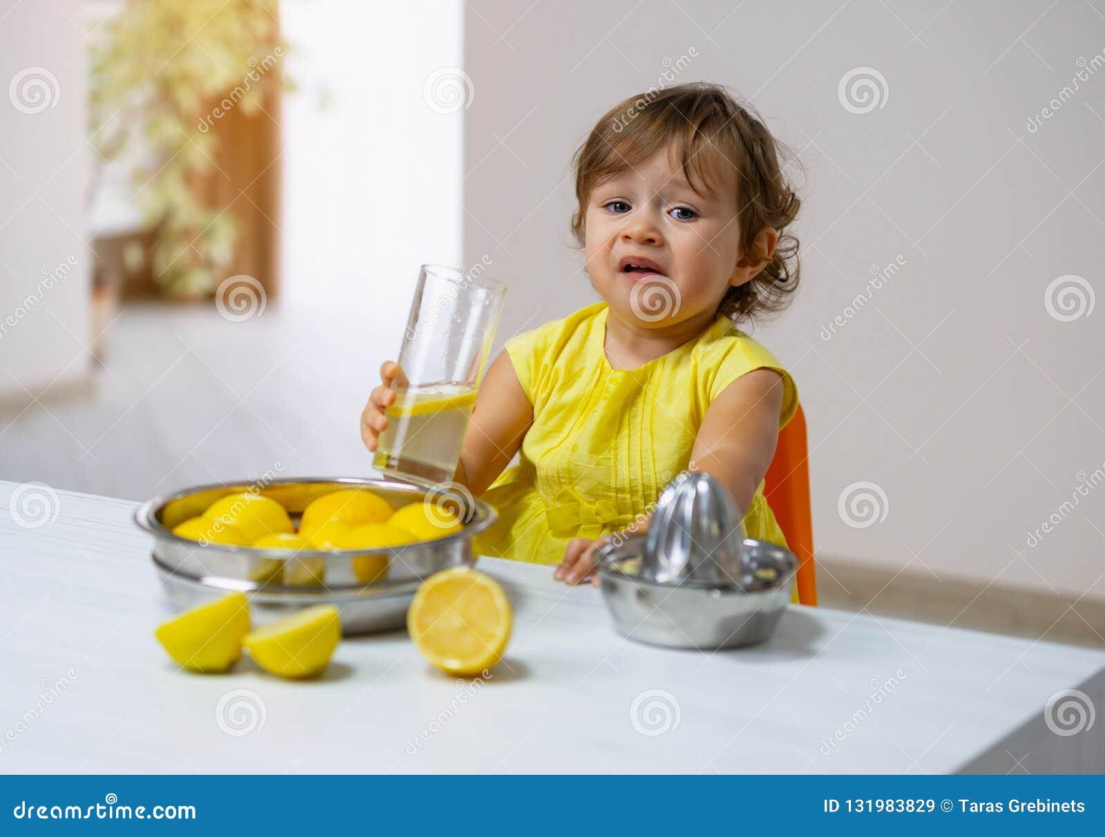 Lite smakar flickan i en gul klänning den lagade mat lemonaden
