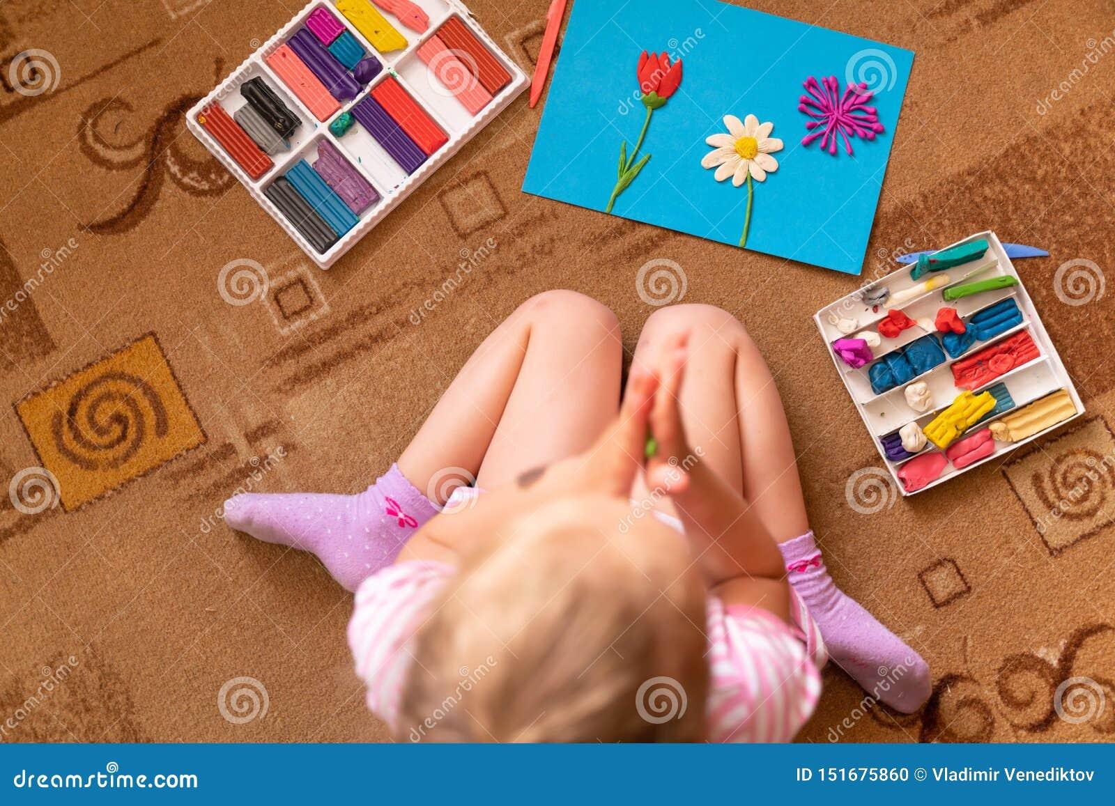 Lite spelar hugger flickan och från lera modellera av plasticine och utvecklingen av fin motorexpertis