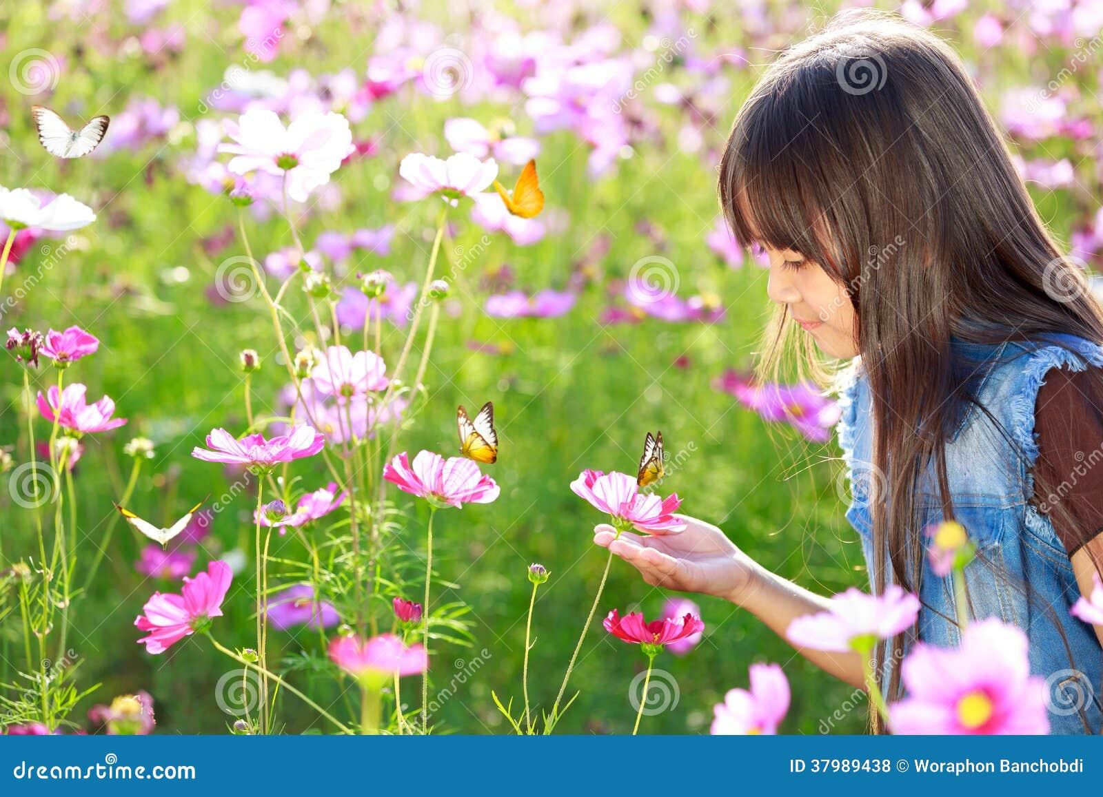 Liten asiatisk flicka i blommafält