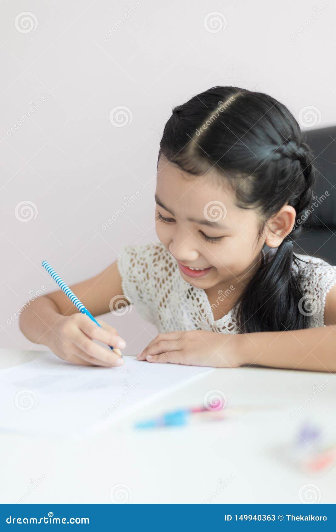 Liten asiatisk flicka som använder blyertspennan för att skriva på papperet som gör läxa och leende med lycka för det valda utbil