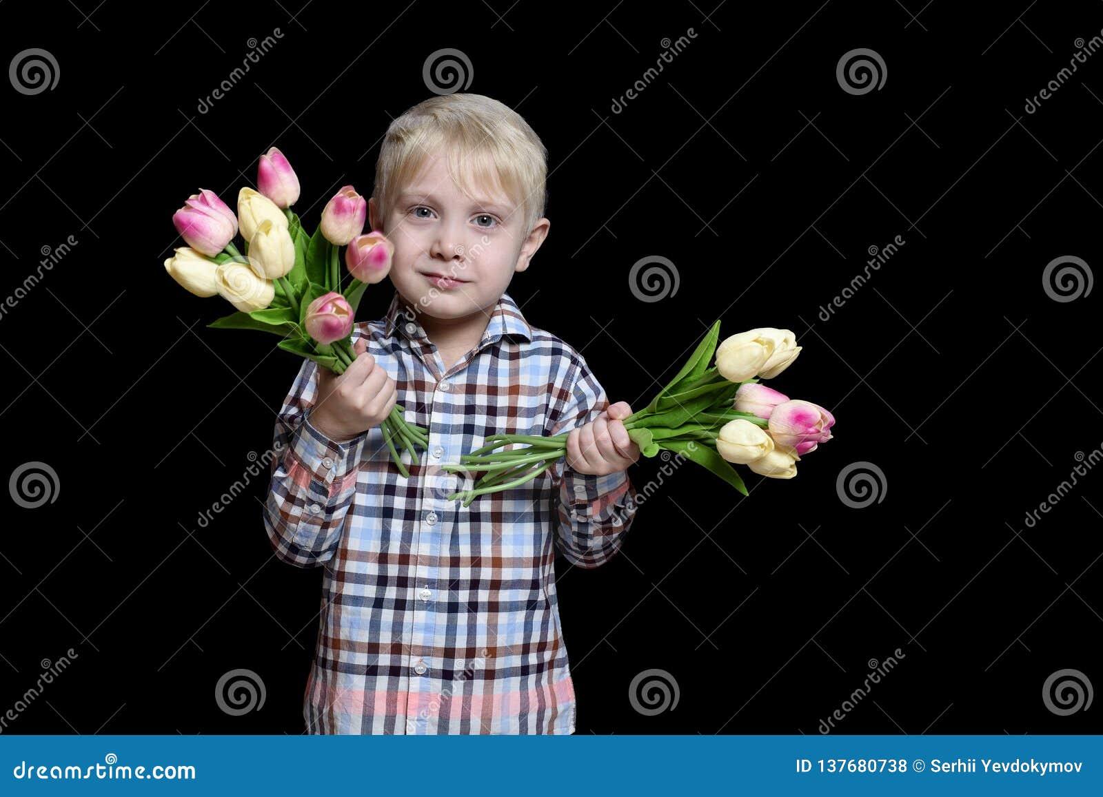 Liten blond pojke som rymmer två buketter av tulpan Stående Isolat på svart bakgrund