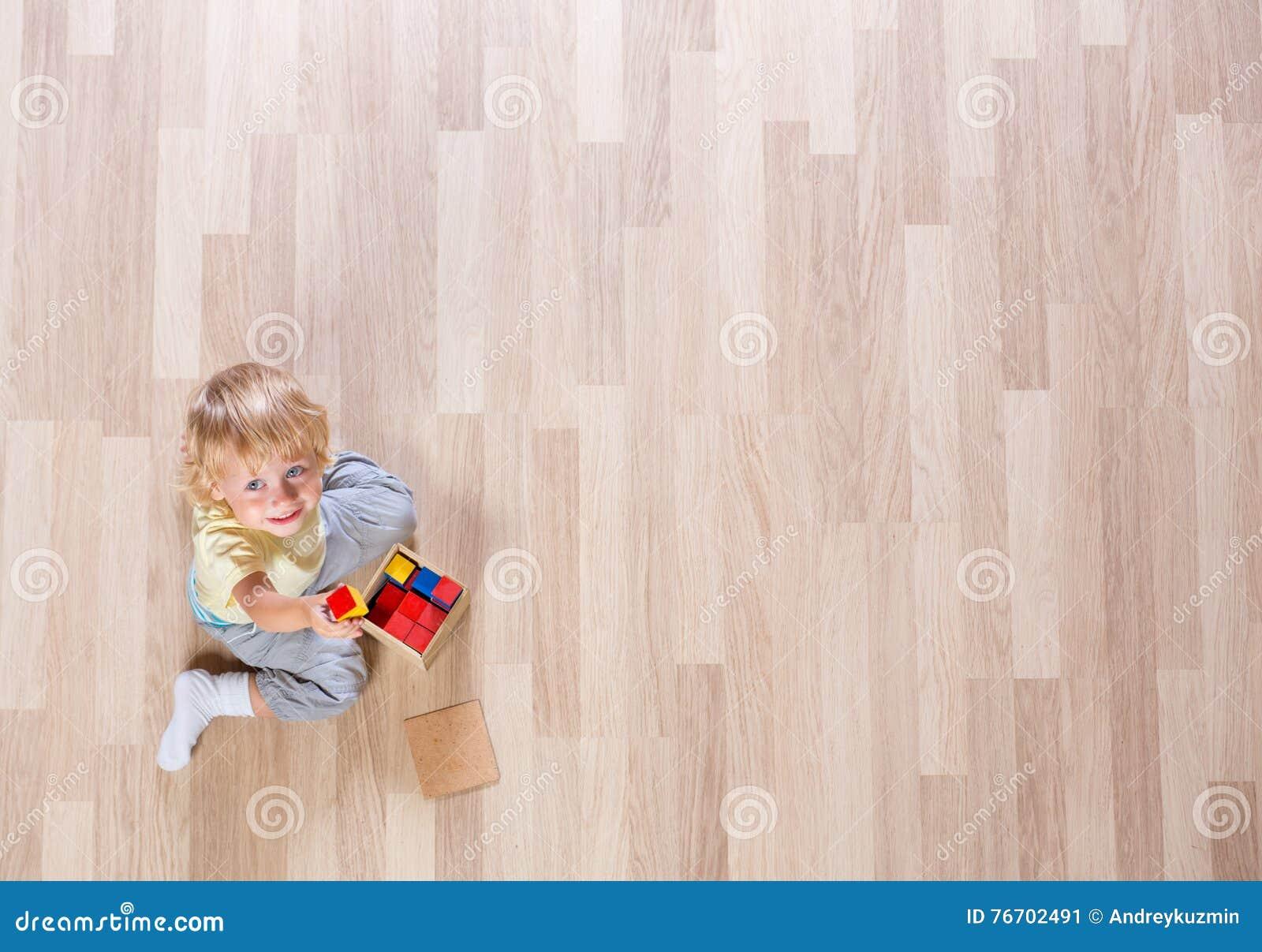 Liten blond ungepojke som spelar med färgrika byggnadskvarter på bästa sikt för golv