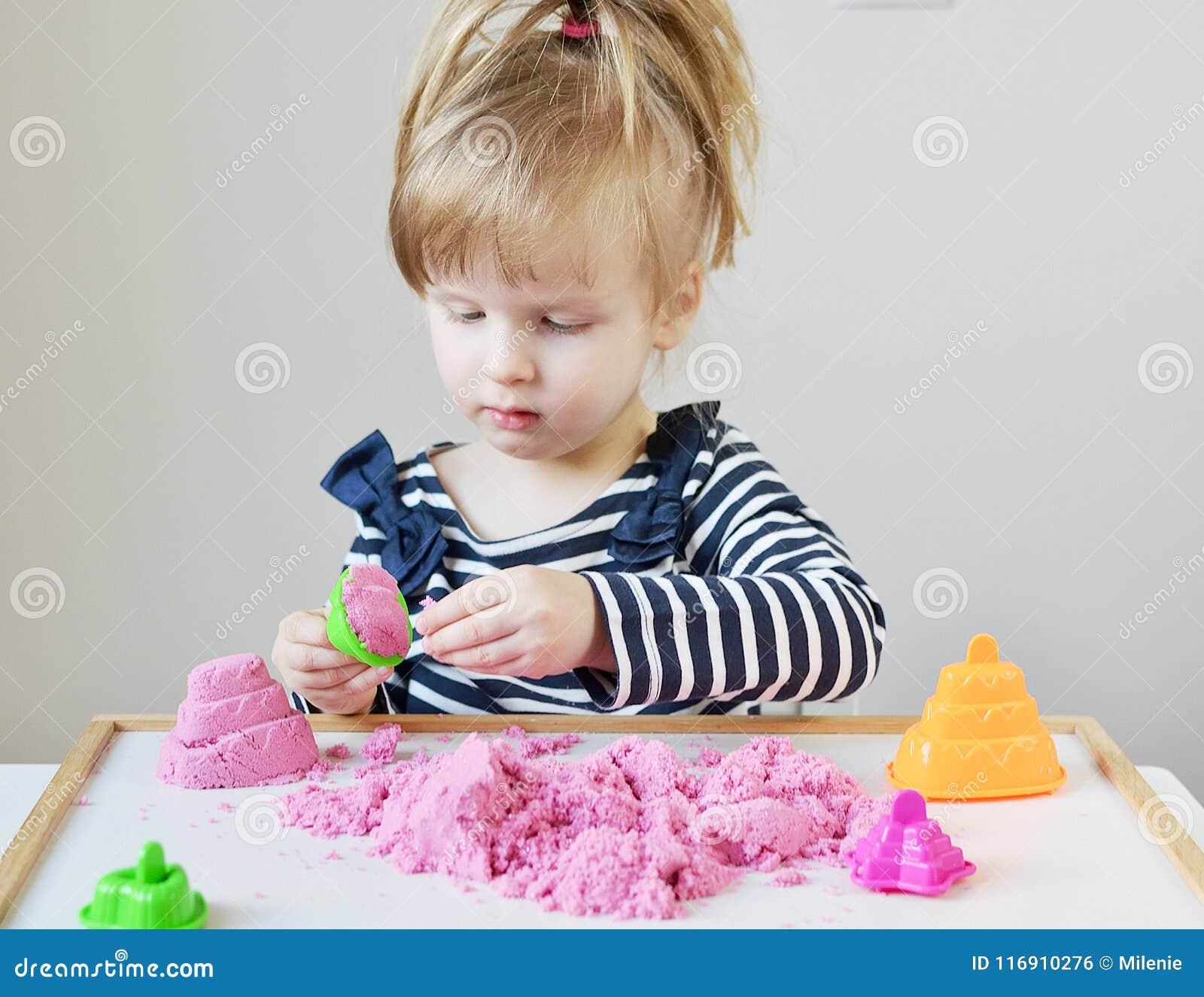 Liten Caucasian flicka som spelar med hemmastadd rosa kinetisk sand