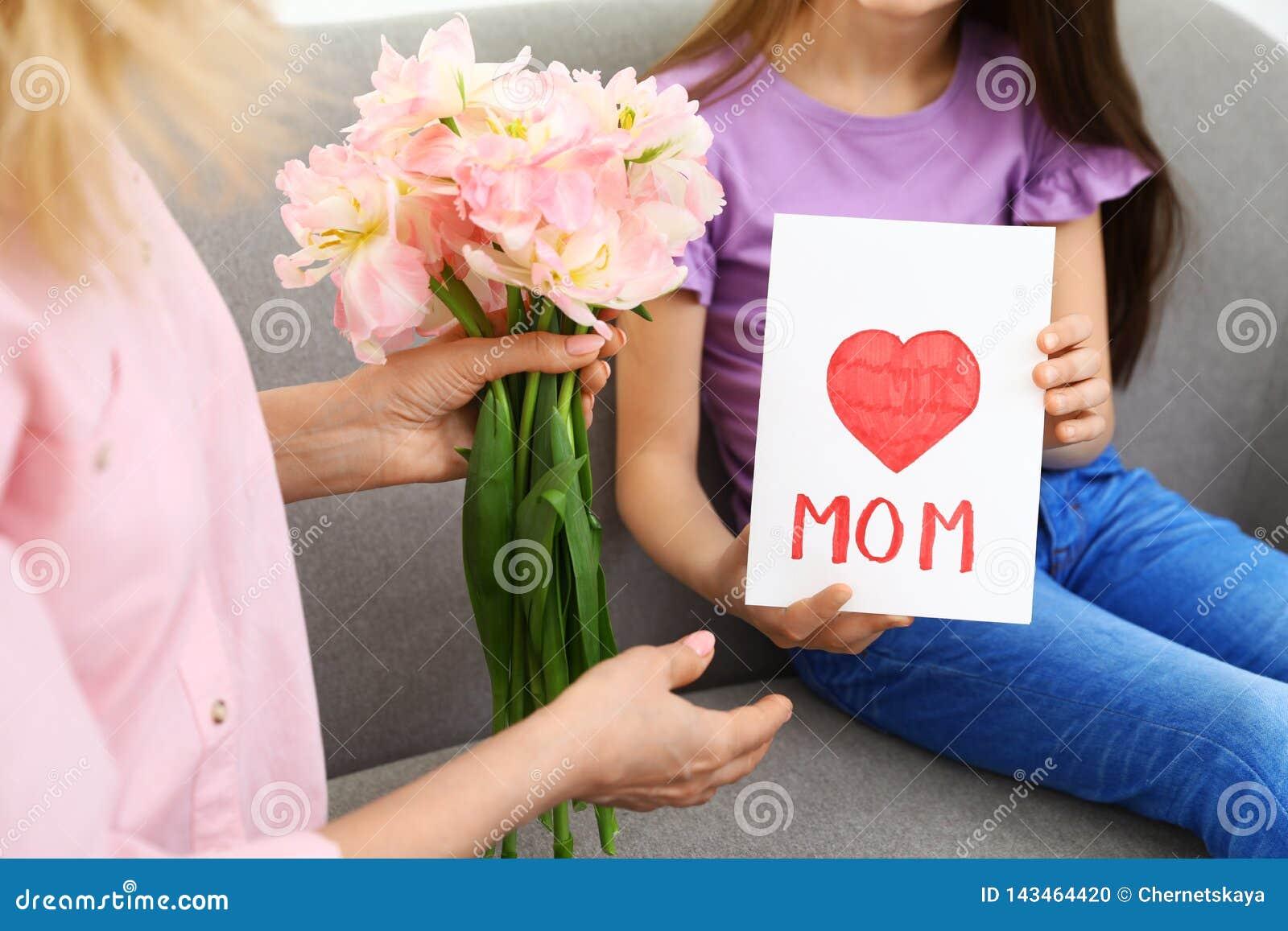 Liten dotter som hemma gratulerar hennes mogna mamma lycklig moder s för dag