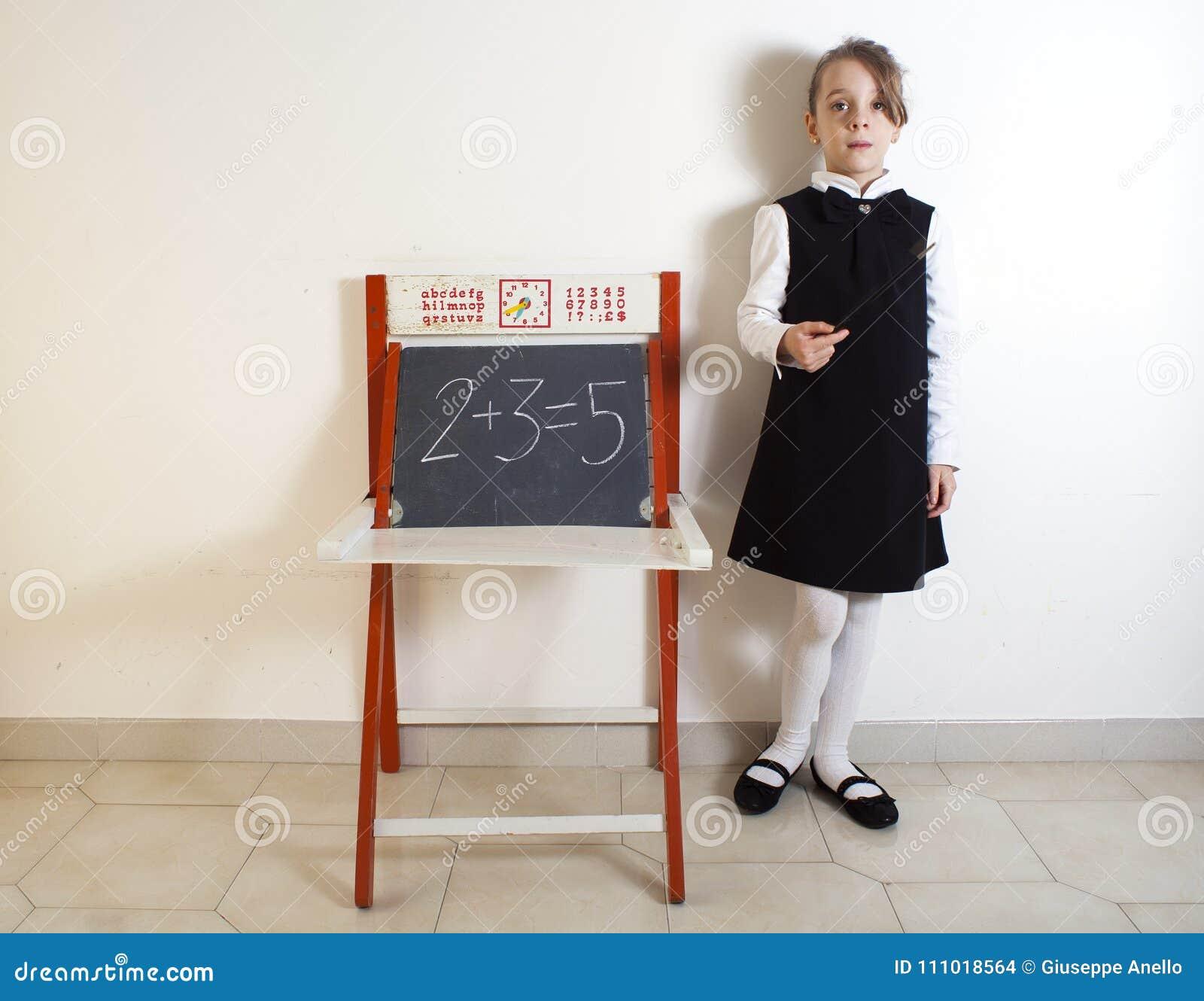 Liten flicka bredvid den svart tavlan