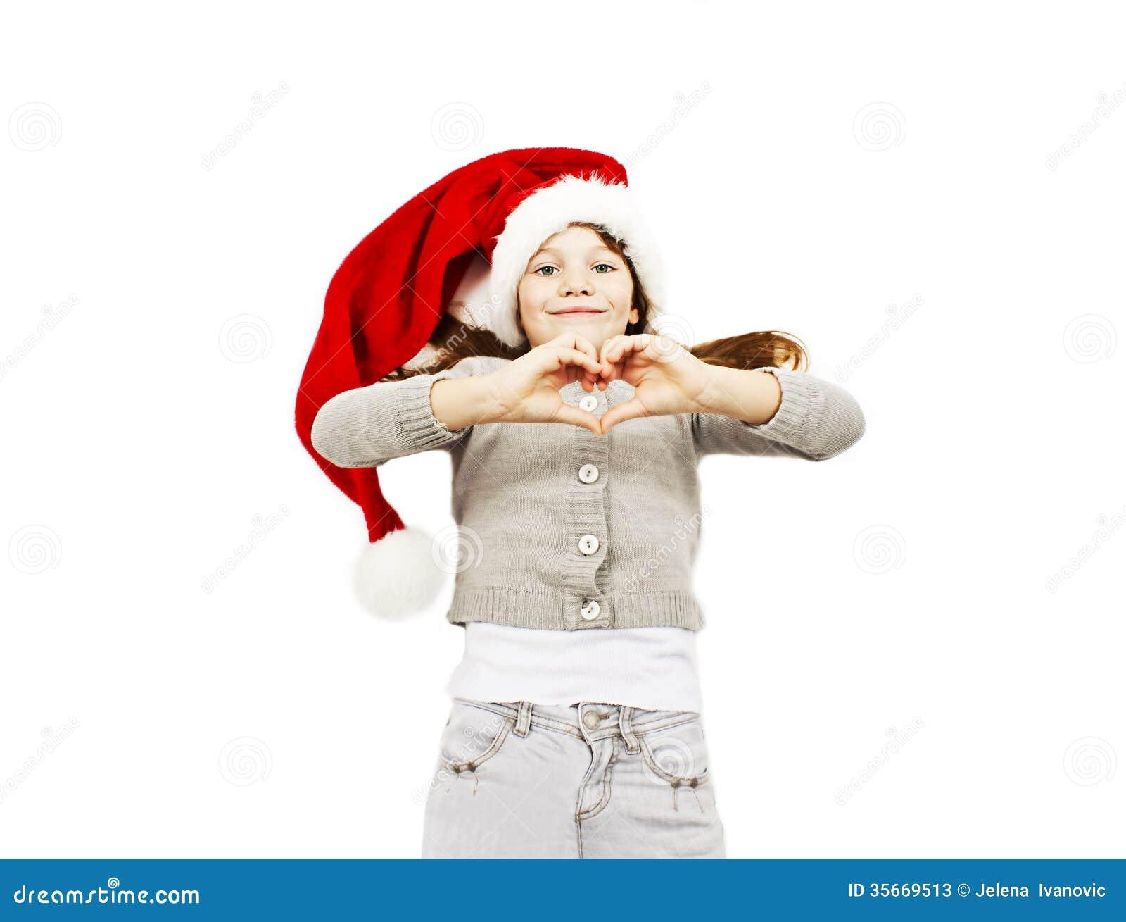 Liten flicka i den röda jultomtenhatten som gör hjärtan med henne händer