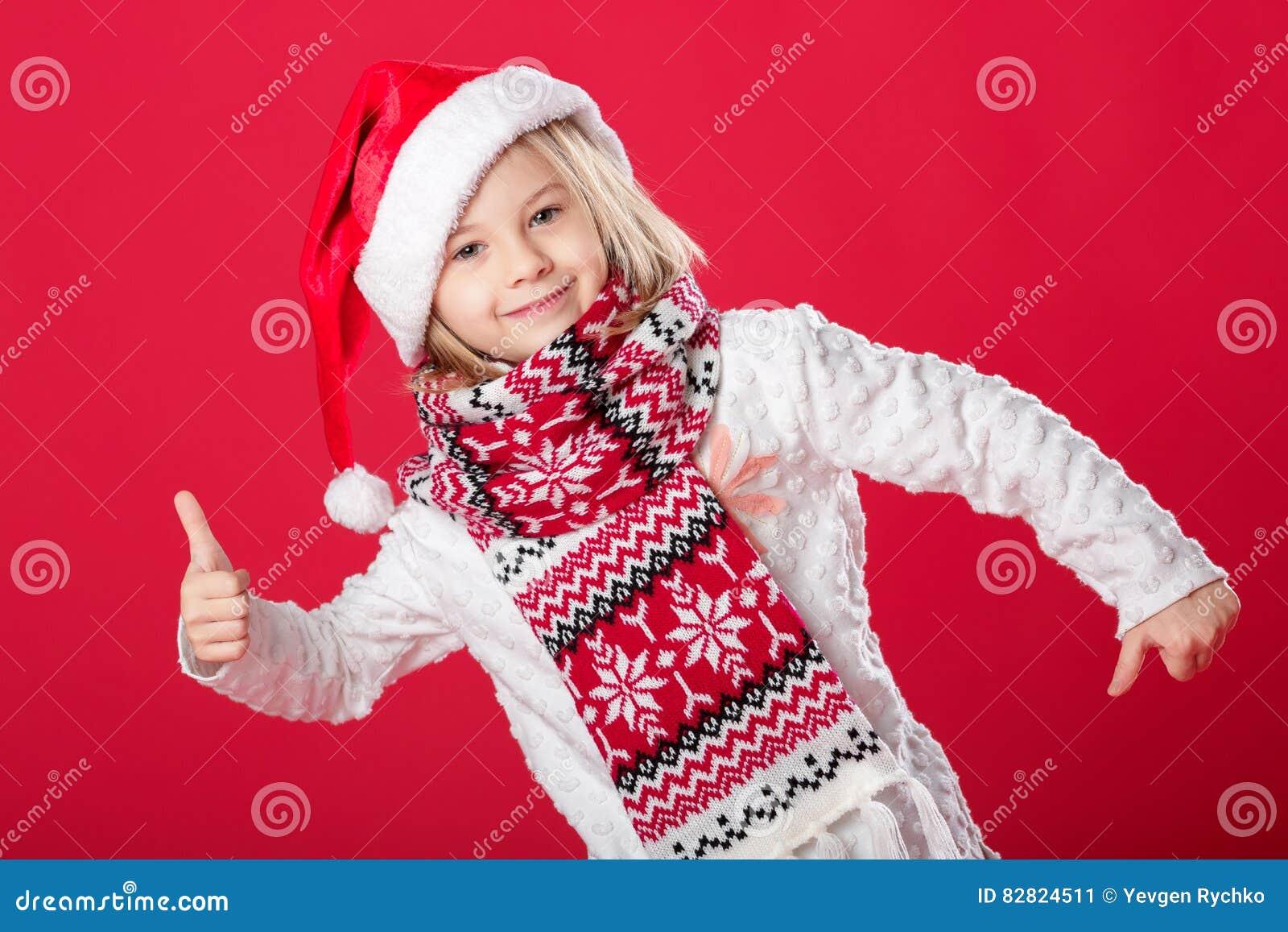 Liten flicka i den santa hatten och halsduken på röd bakgrund