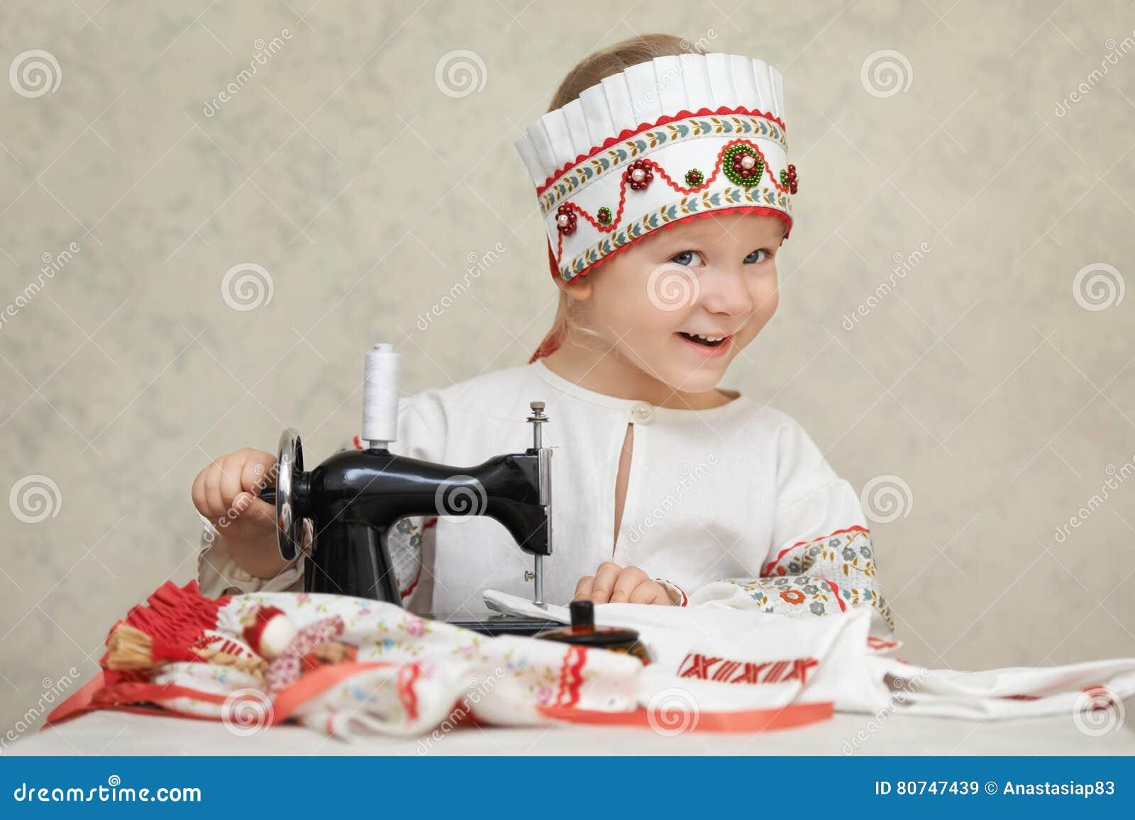 Liten flicka i den traditionella ryssskjortan och kokoshnik på processen av sömnaden