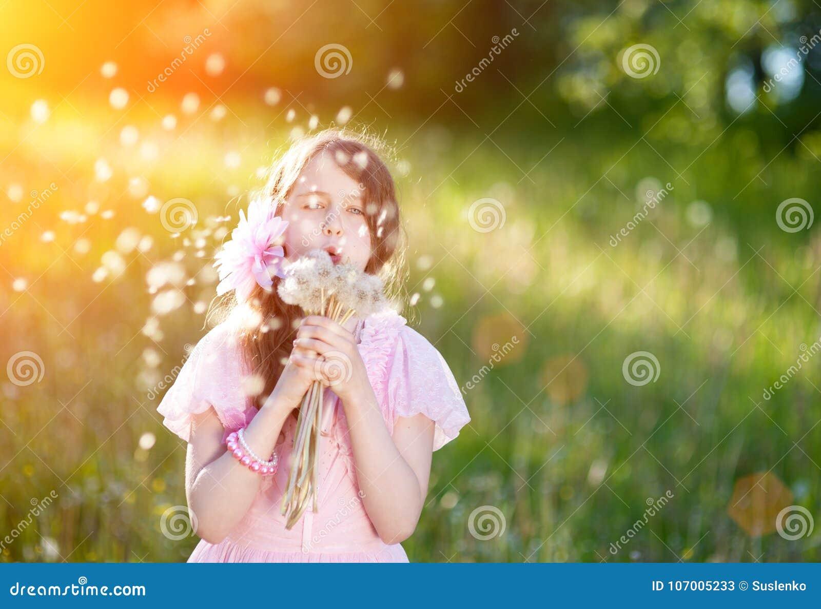 Liten flicka i en rosa klänning som blåser en bukett av maskrosor i strålarna av en ljus sol