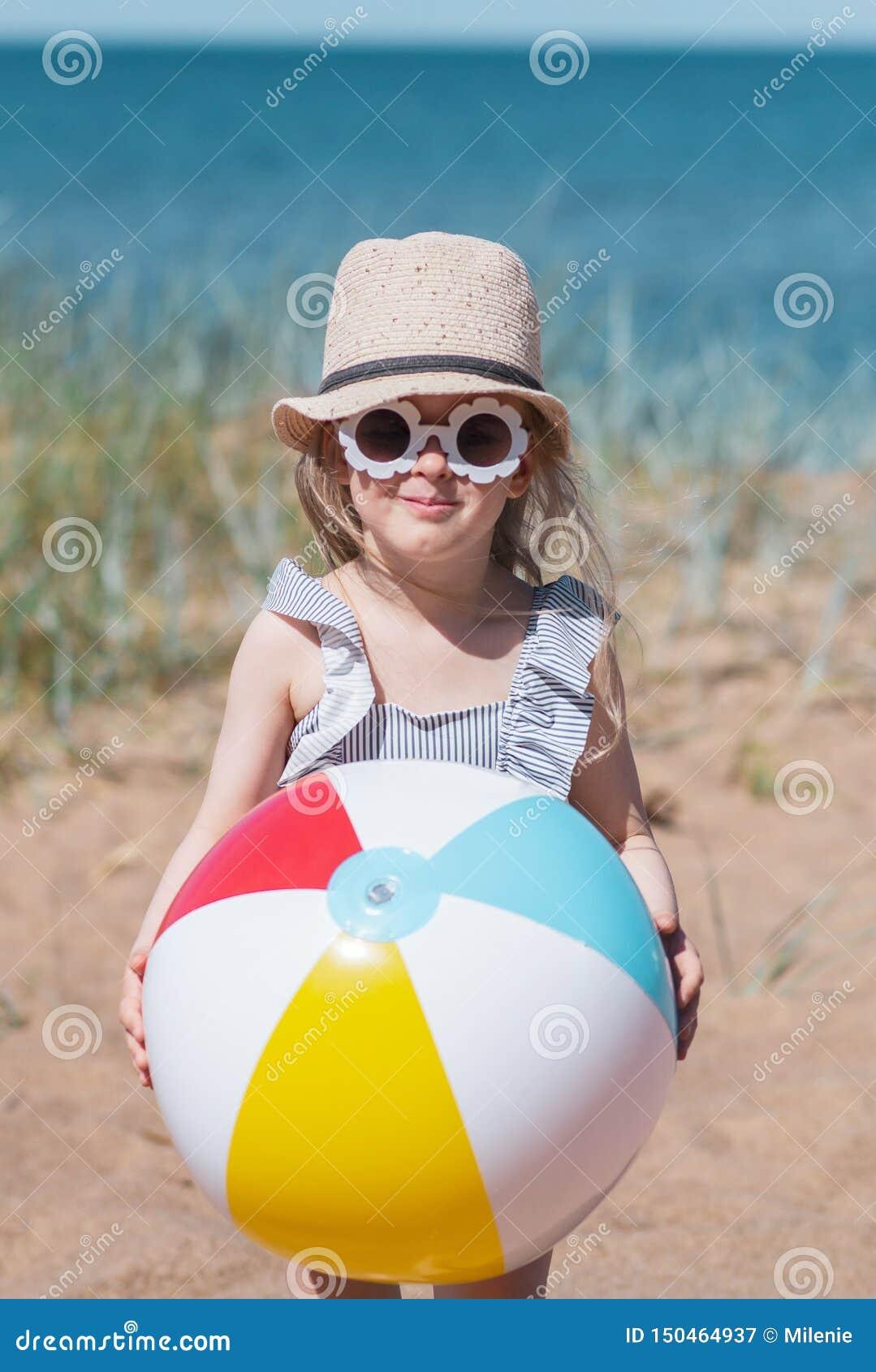Liten flicka i hatten som spelar på stranden med bollen, solig sommardag