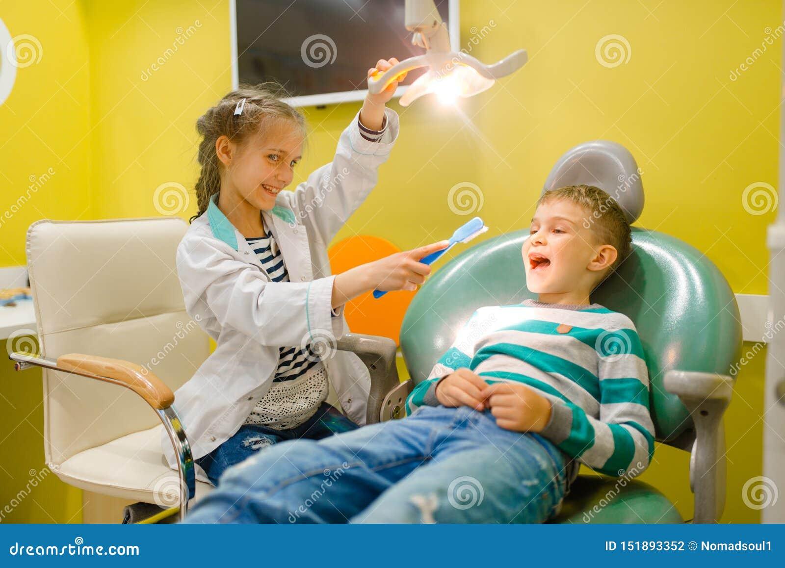 Liten flicka i likformign som spelar tandläkaren, lekrum