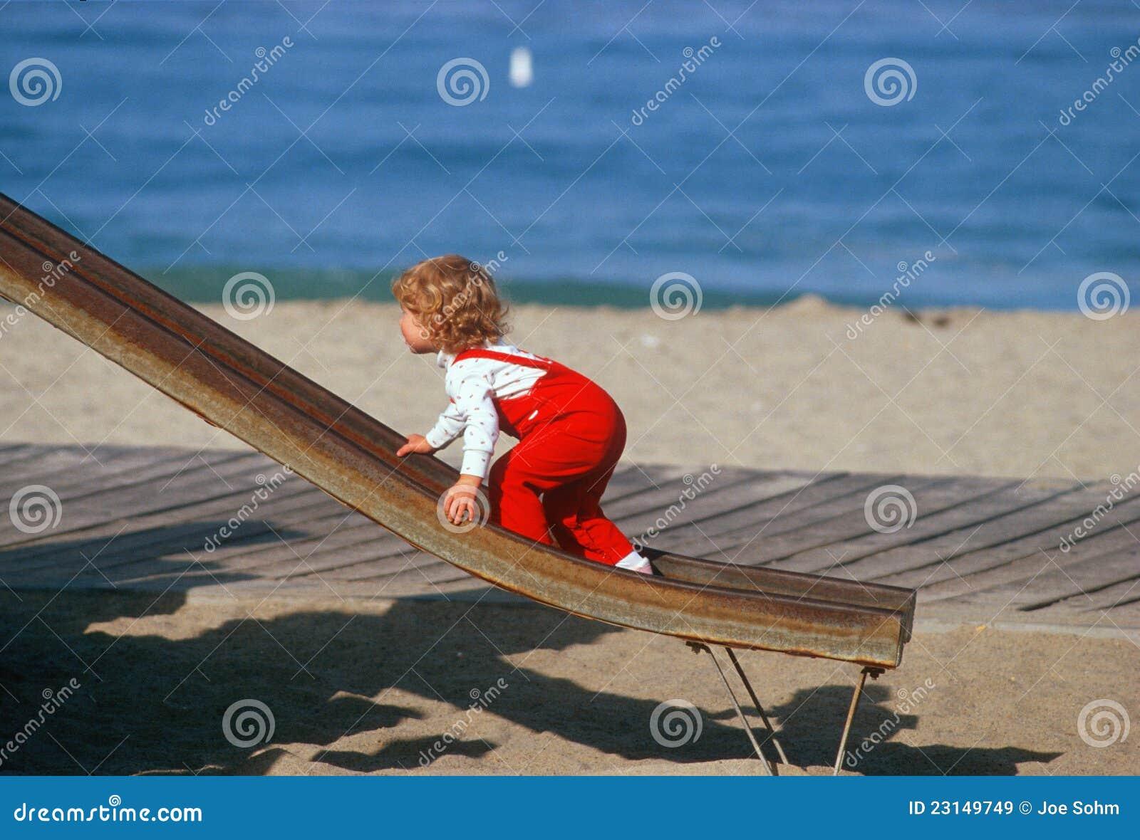 Liten flicka i röda overralls som klättrar upp glidbana