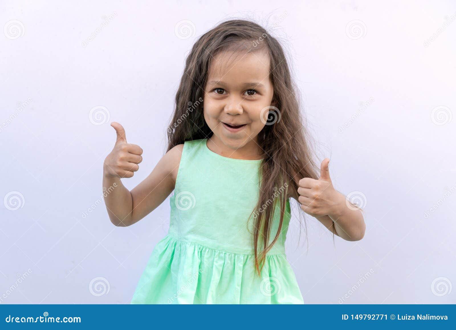 Liten flicka med brunt långt lockigt hår som isoleras på vit bakgrund Unge som ger upp tv? tummar