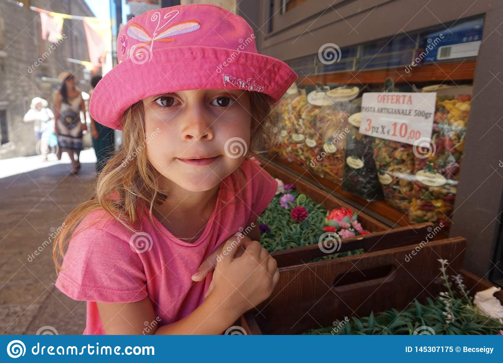 Liten flicka med den rosa hatten framme av en livsmedelsbutik, San Marino